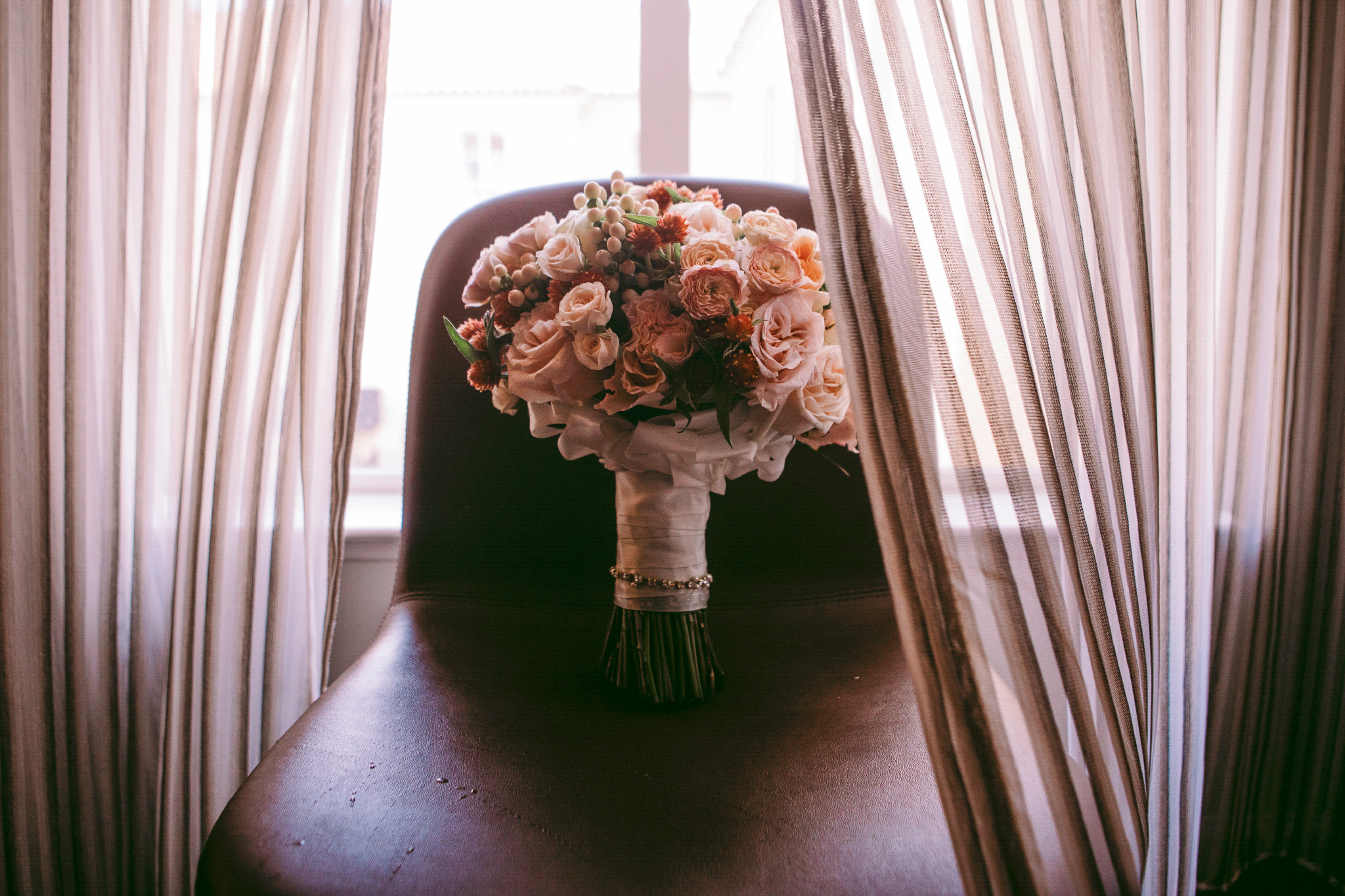san diego wedding   photographer | bouquet of pink flowers sitting on leather chair by the window