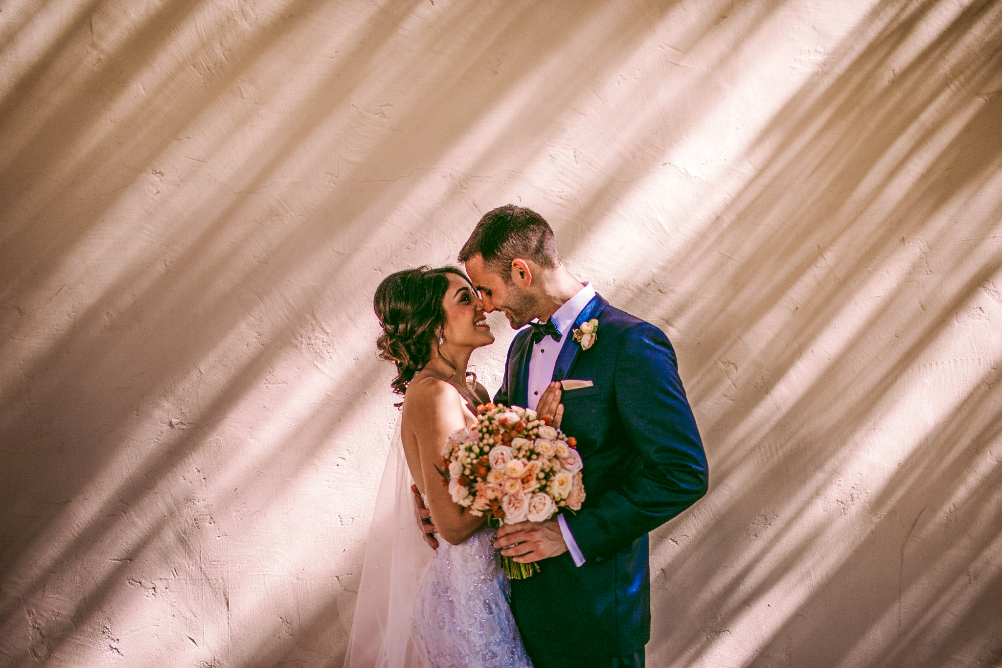 san diego wedding   photographer | couple with man holding bouquet of flowers about to kiss