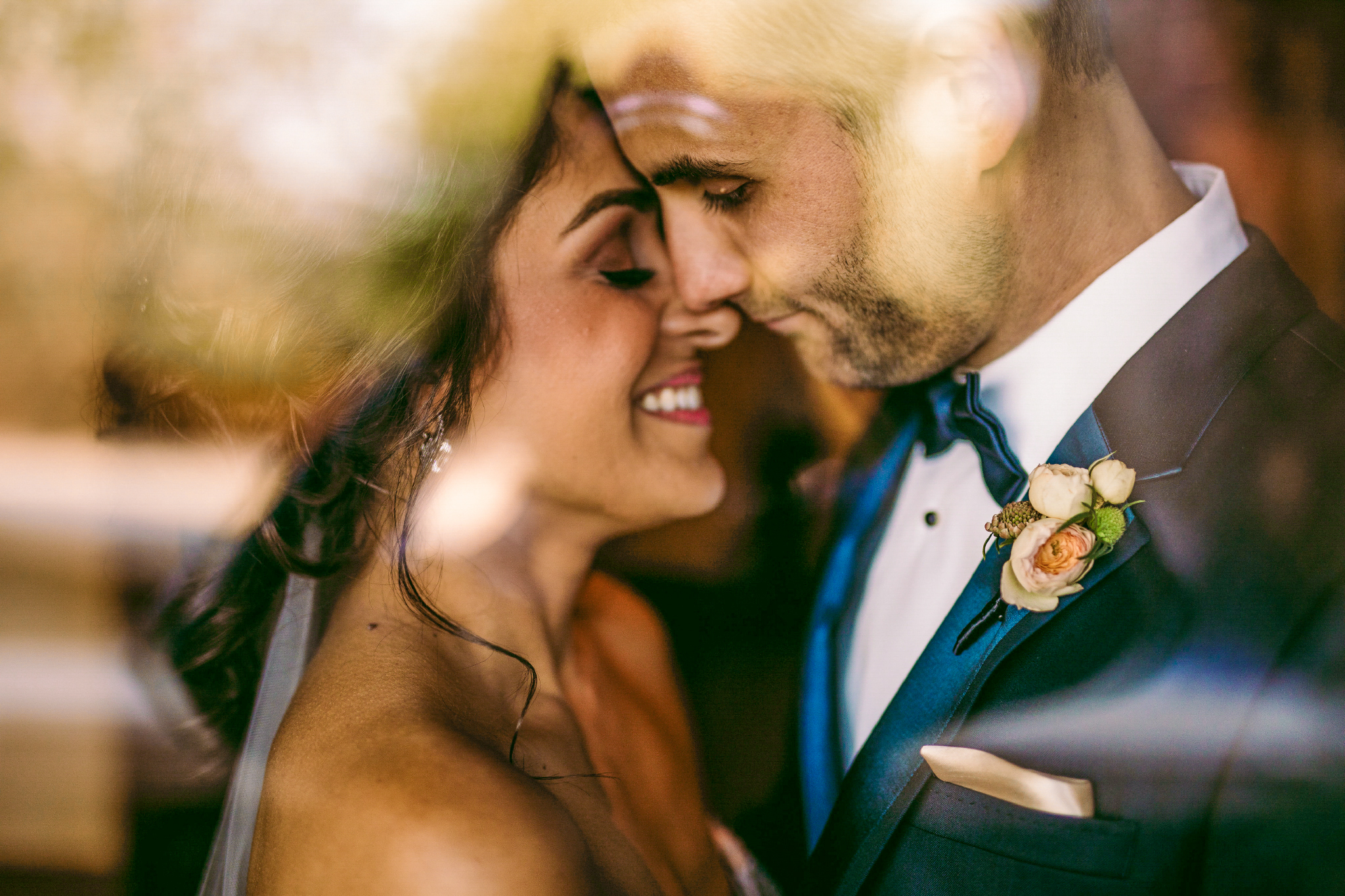san diego wedding   photographer | man in blue suit with flowers about to kiss woman seen through   glass