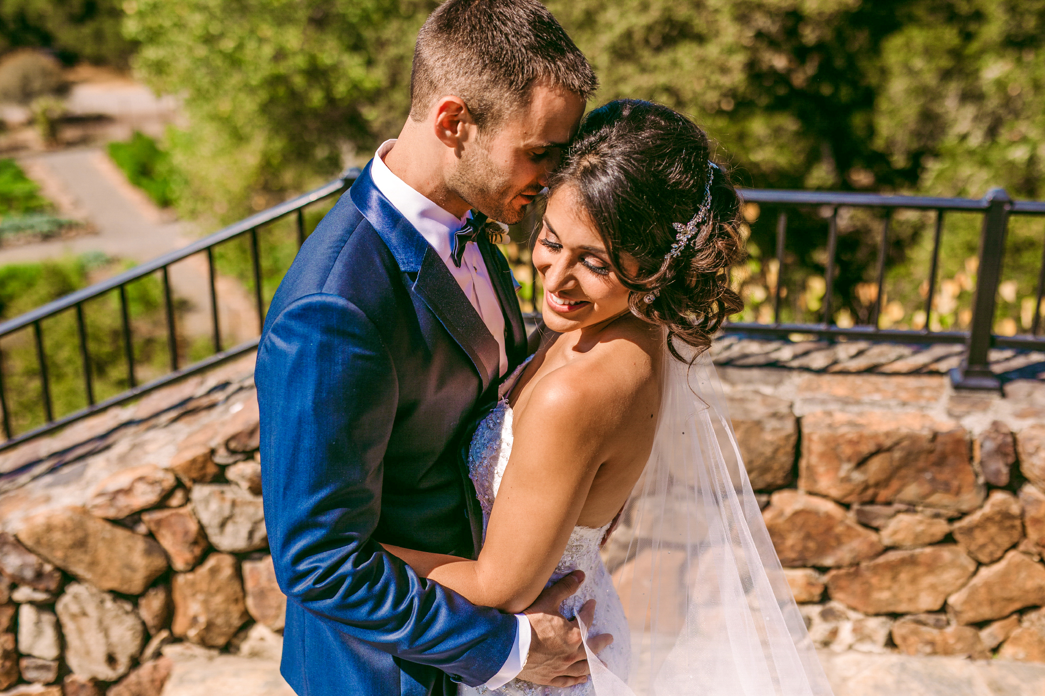 san diego wedding   photographer | man about to kiss woman while holding her hips with railing in   background