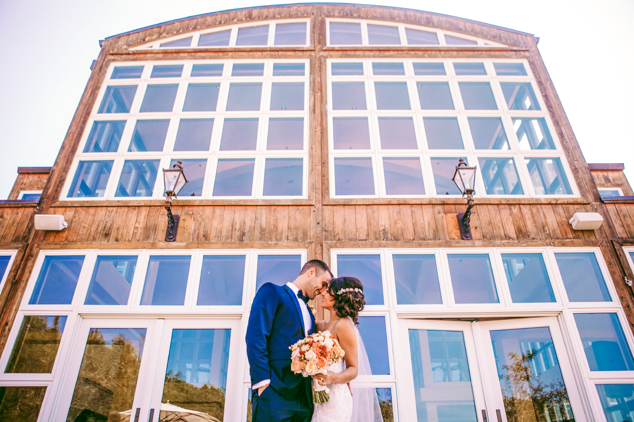 san diego wedding   photographer | couple about to kiss with woman holding bouquet of flowers in   front of building with glass windows