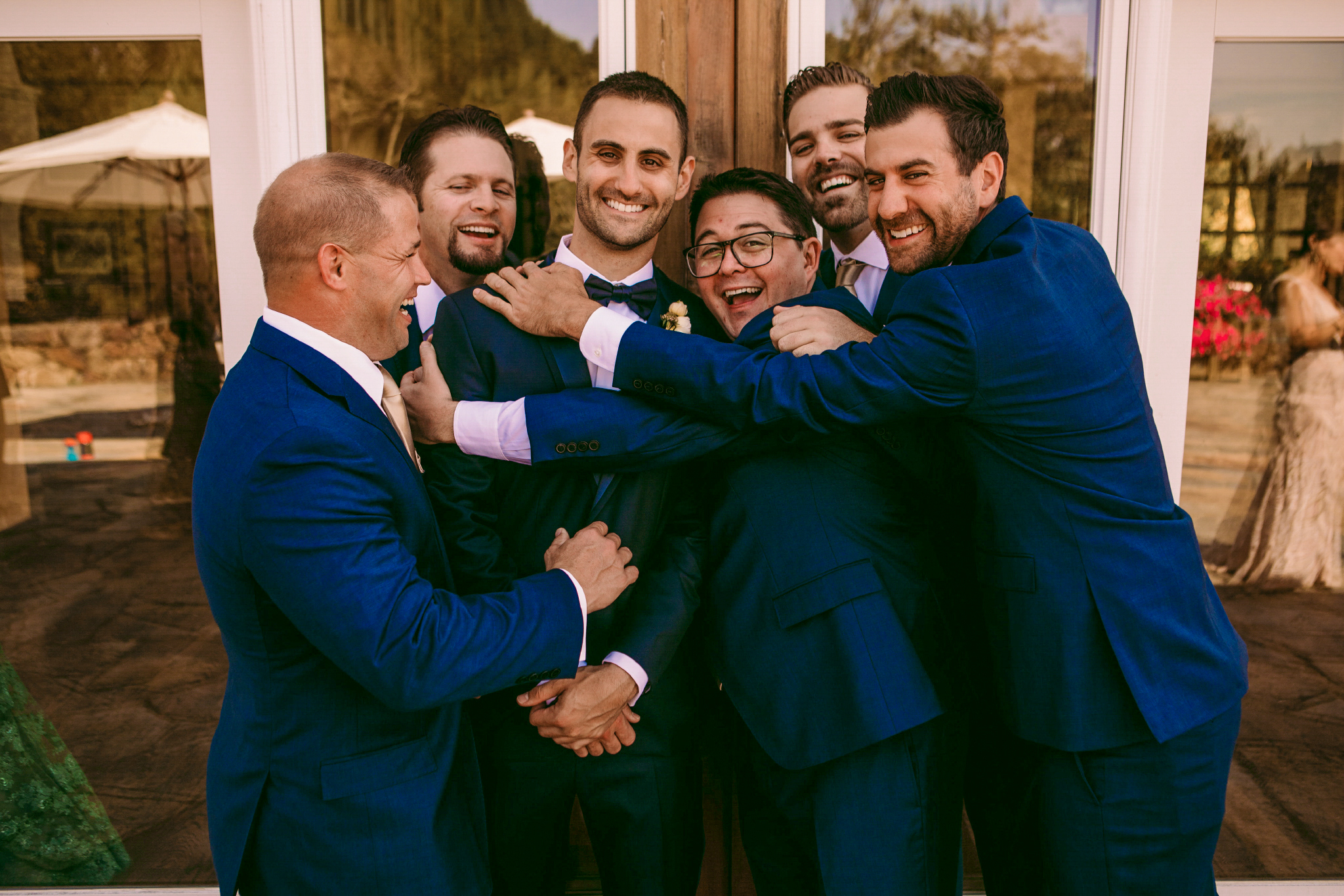 san diego wedding   photographer | group of men in blue suits hugging in front of building with   glass windows