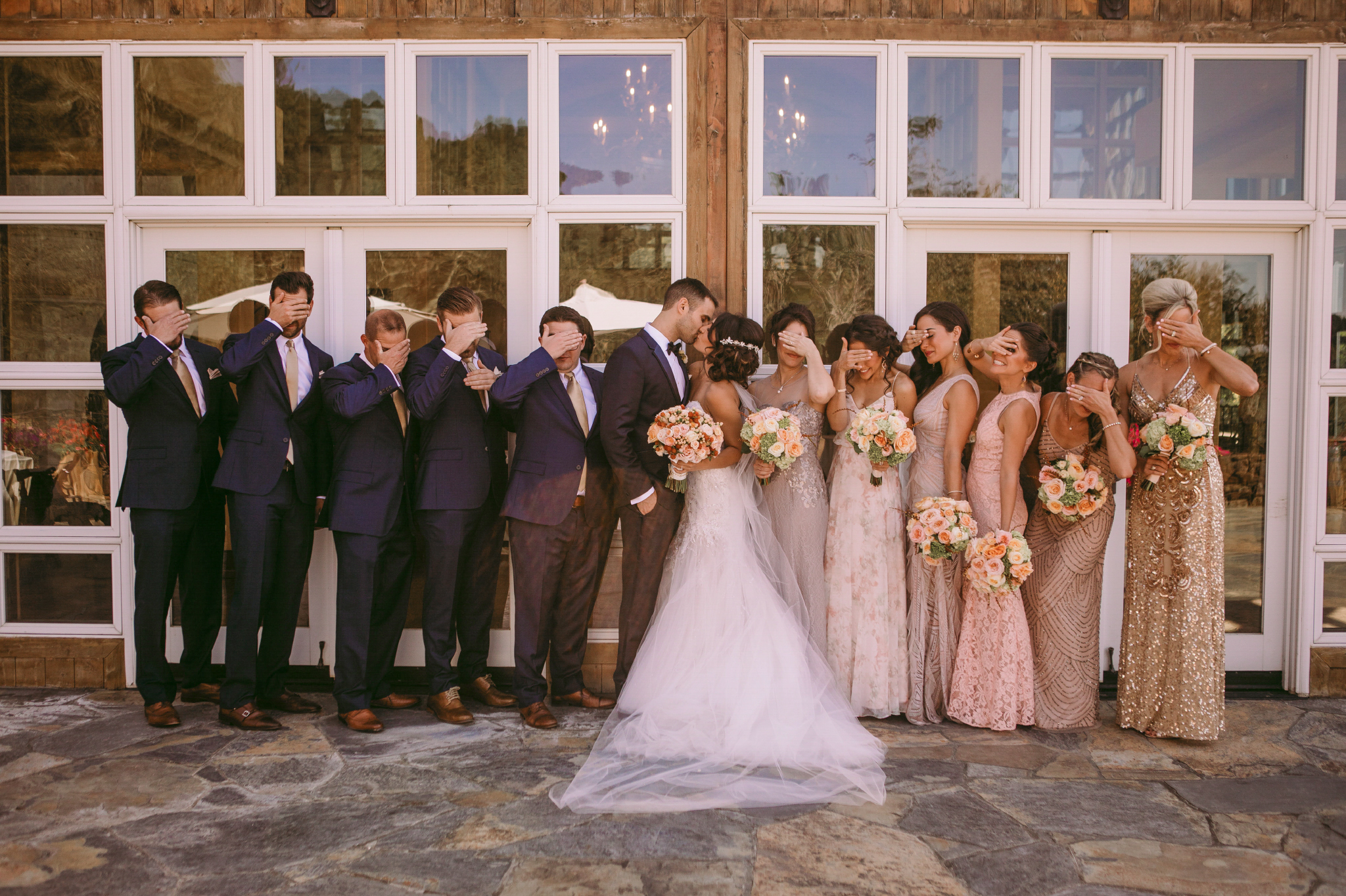 san diego wedding   photographer | couple kissing in front of group of people covering their eyes