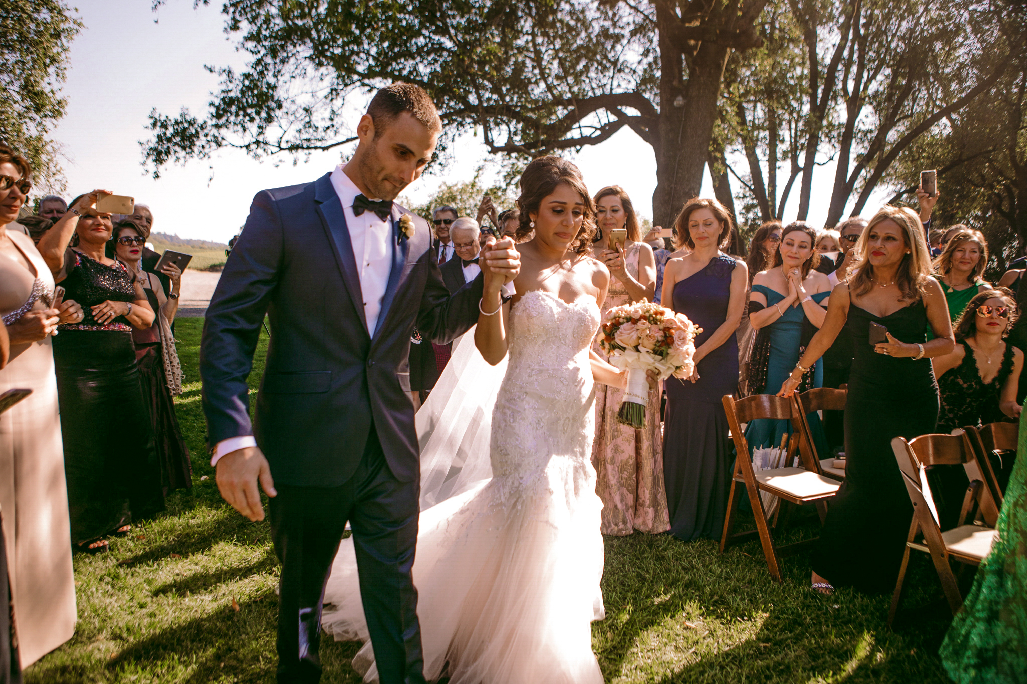 san diego wedding   photographer | groom holding bride's hand as they walk down the aisle