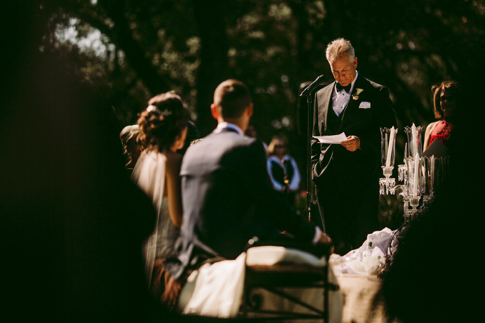 san diego wedding   photographer | man in suit in front of crowd looking down at piece of   paper