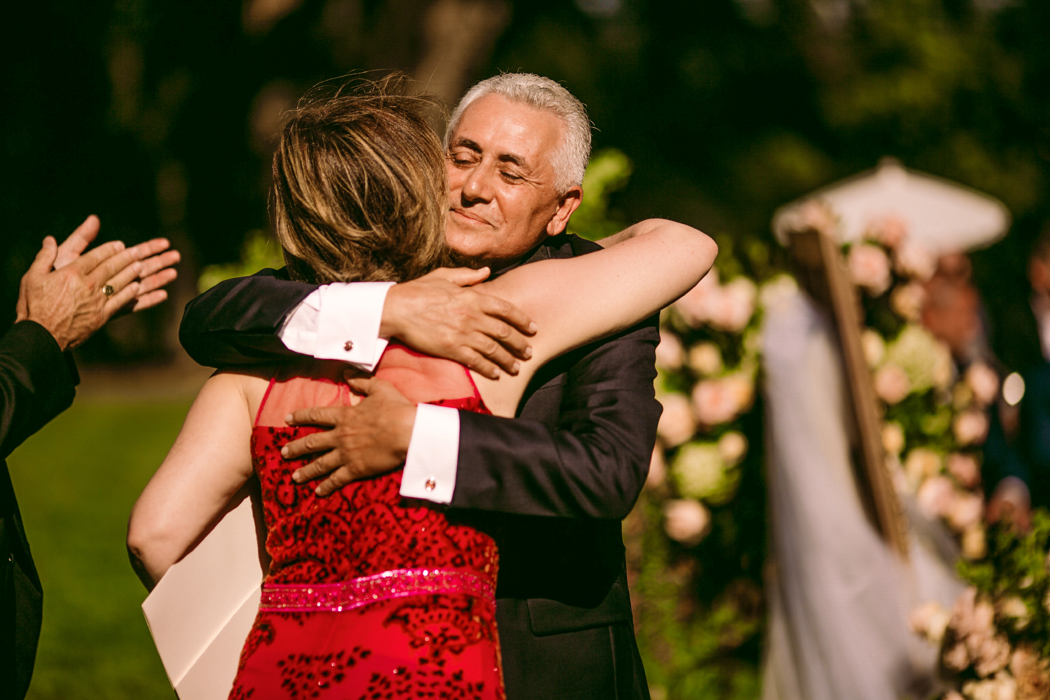 san diego wedding   photographer | woman in red ress faced against camera hugging man in   suit