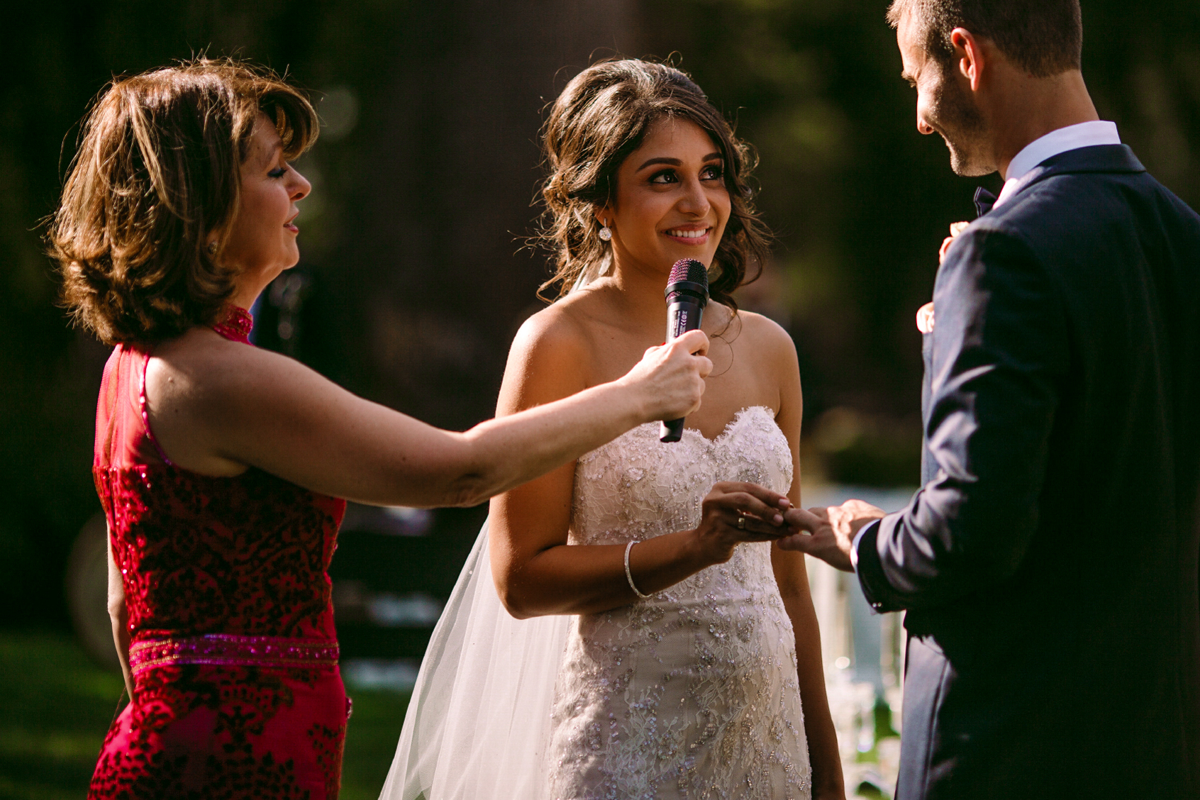 san diego wedding   photographer | woman in red holding mic up to woman's face while woman puts   ring on man's finger