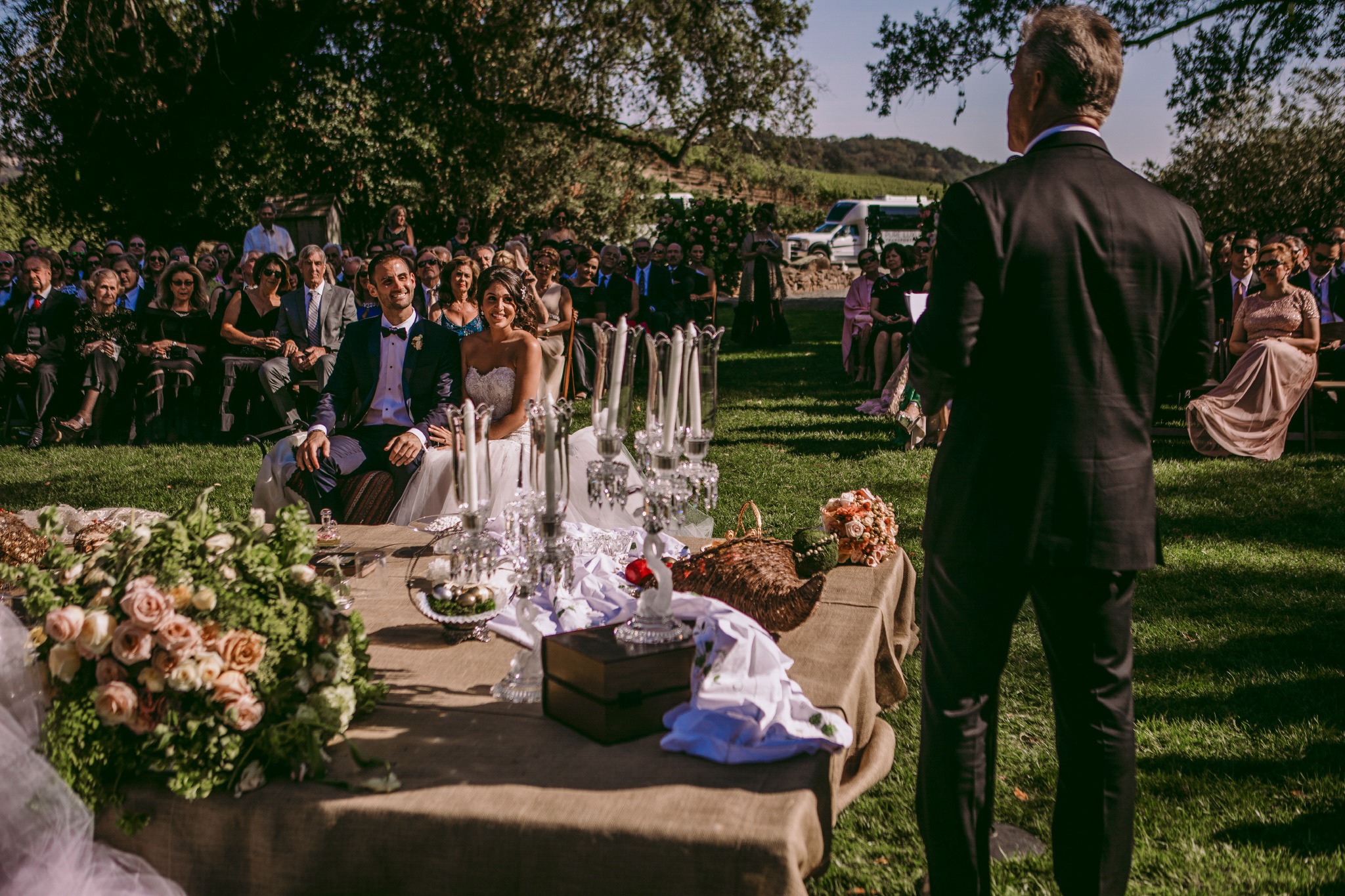 san diego wedding   photographer | bride and groom seated together as they listen to man standing   in front of them