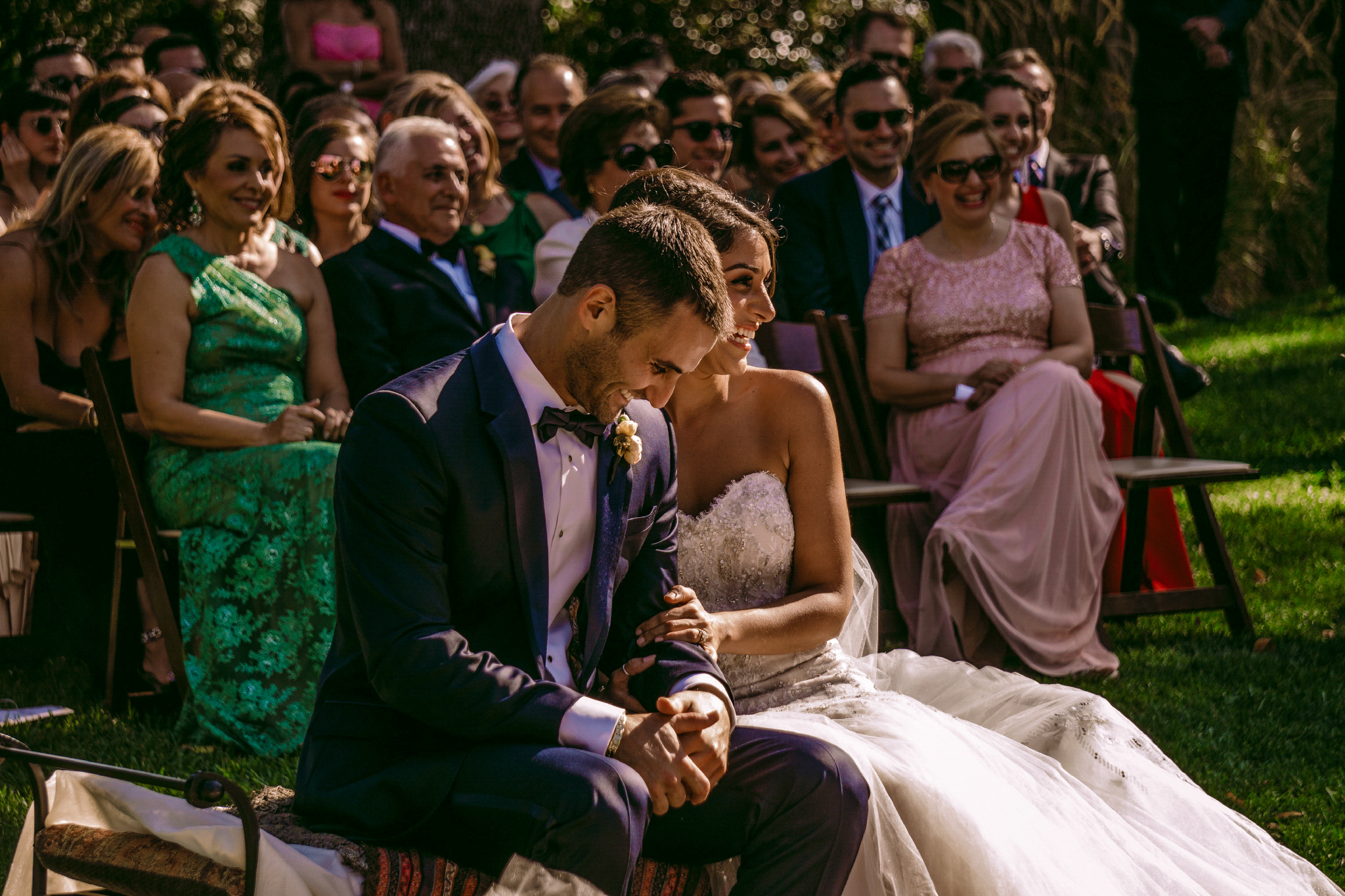 san diego wedding   photographer | married couple sitting in front of crowd while laughing