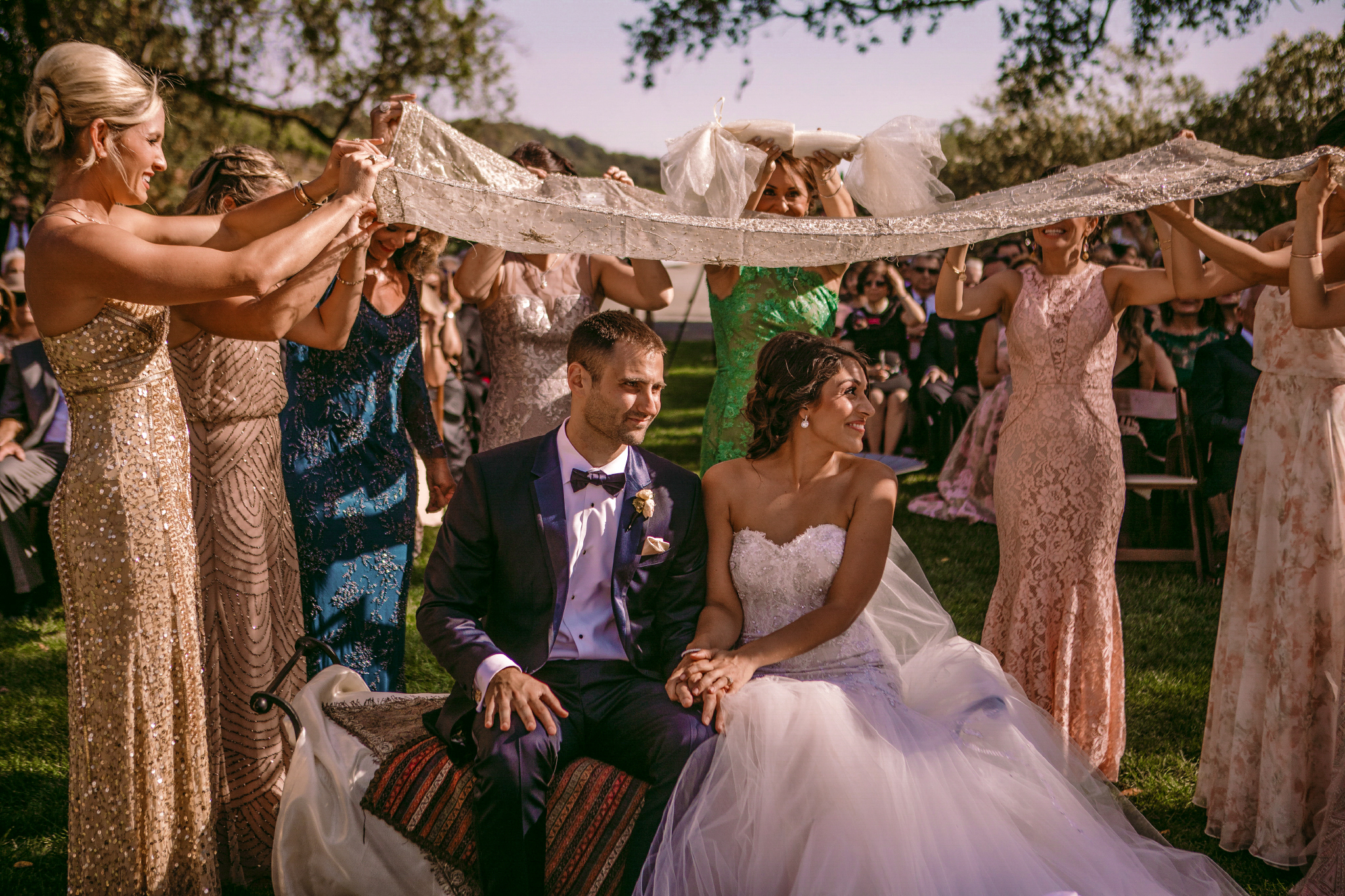 san diego wedding   photographer | married couple sitting down holding hands while under cloth   being held up by women