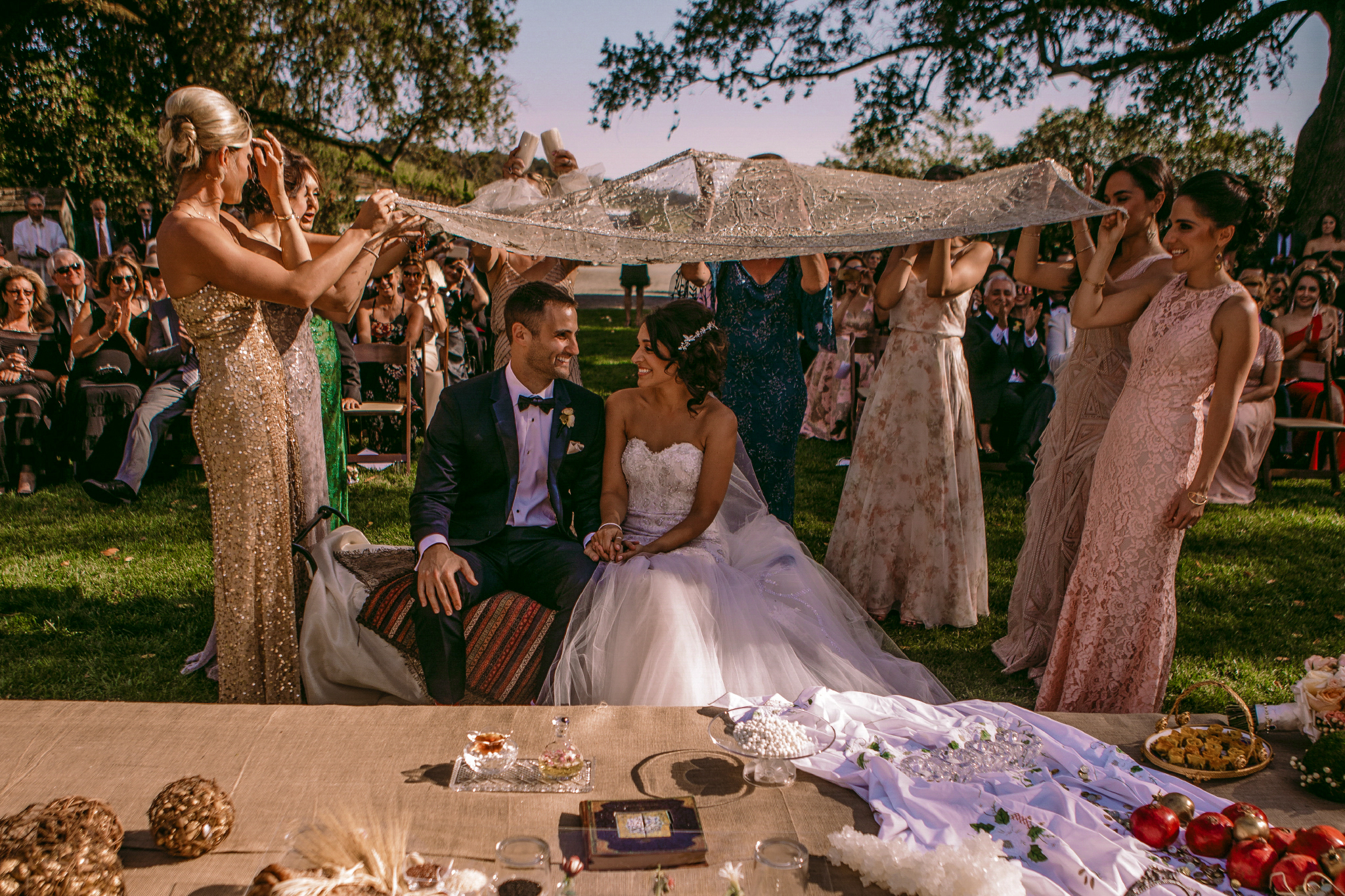 san diego wedding   photographer | married couple sitting down smiling looking at each other   under cloth being help up by women