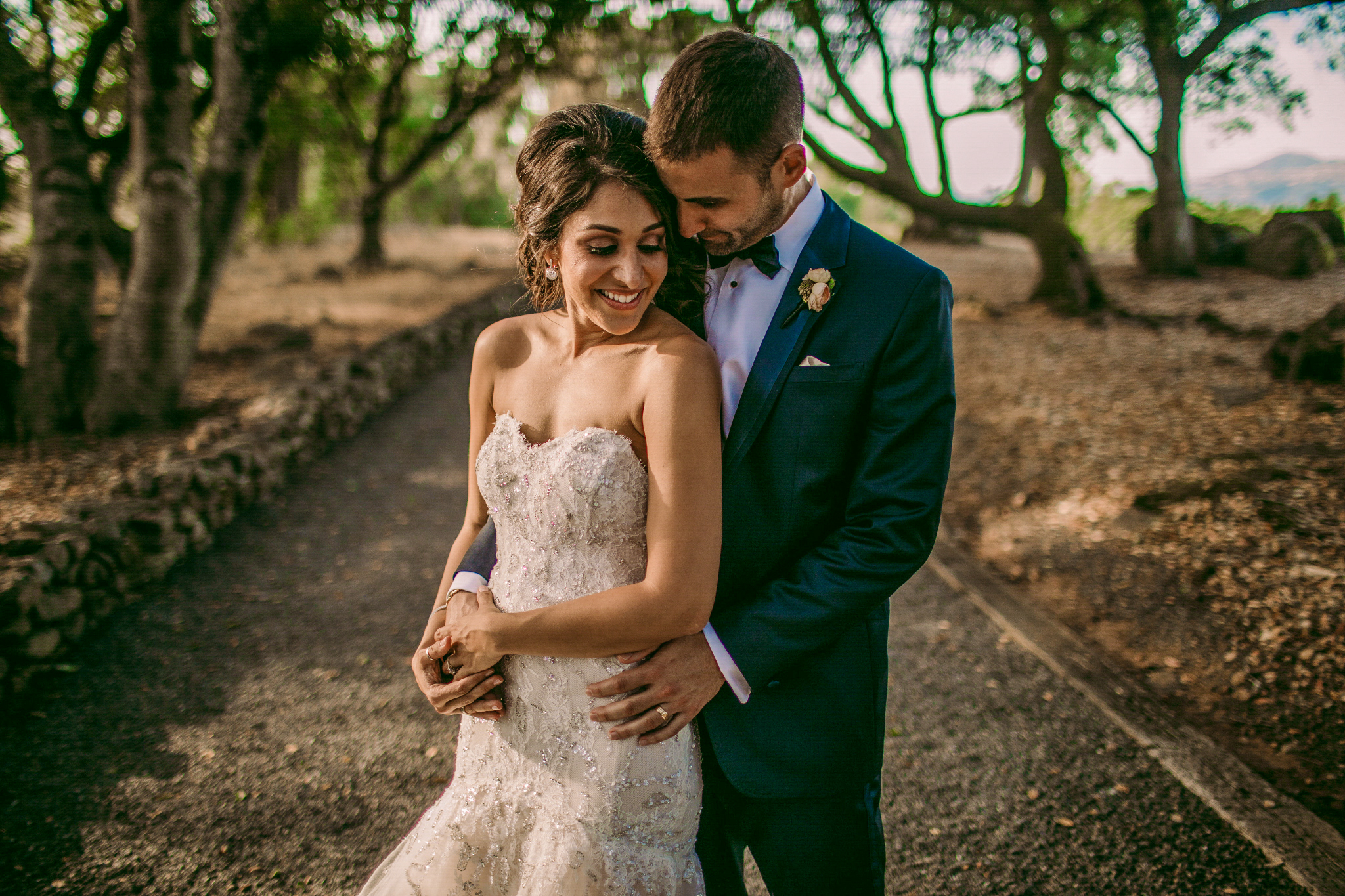 san diego wedding   photographer | married couple man holding woman from behind while holding her   hand with woman smiling looking back