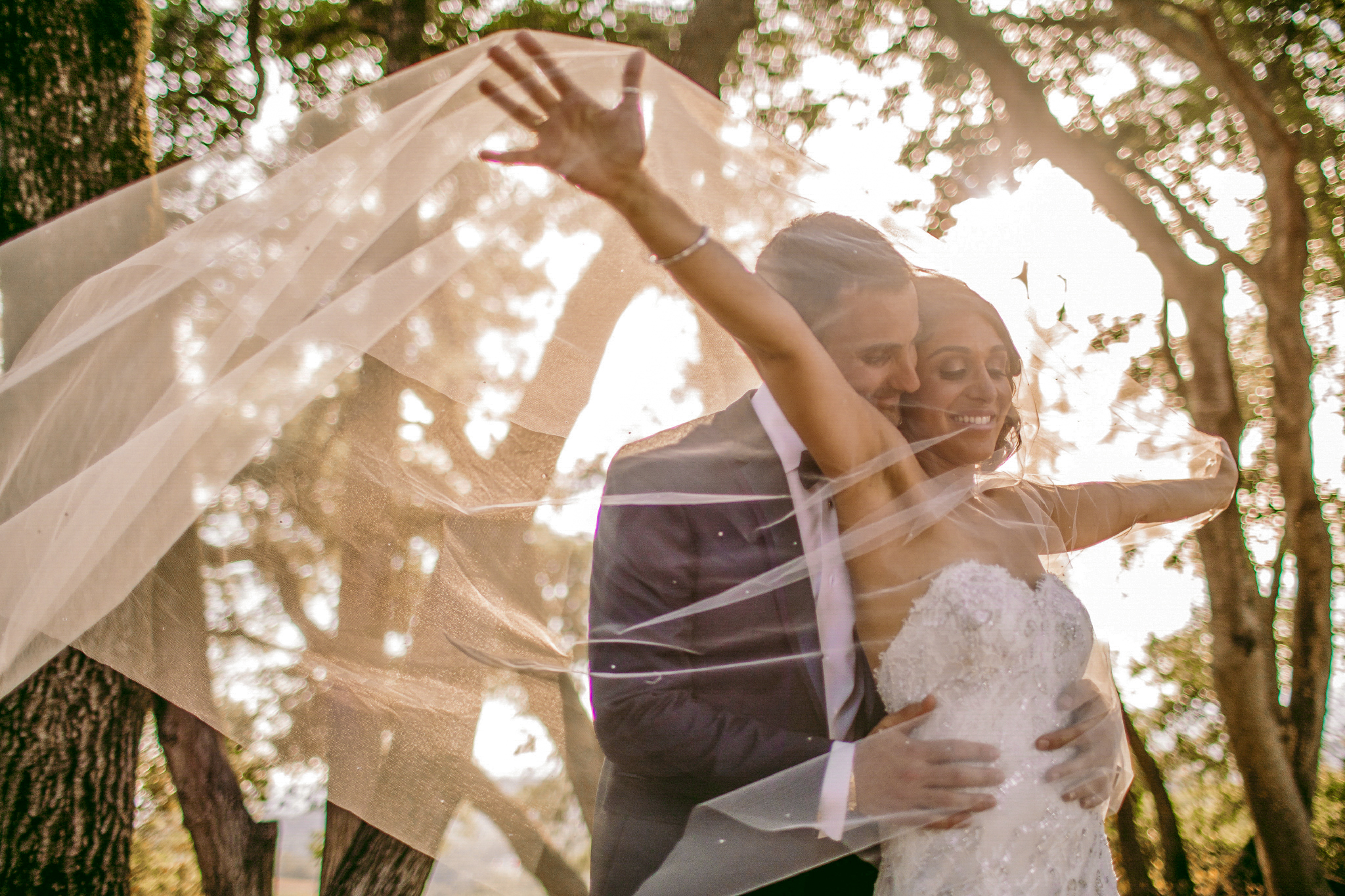san diego wedding   photographer | groom holding bride from behind while under veil with bride's arms up wide open