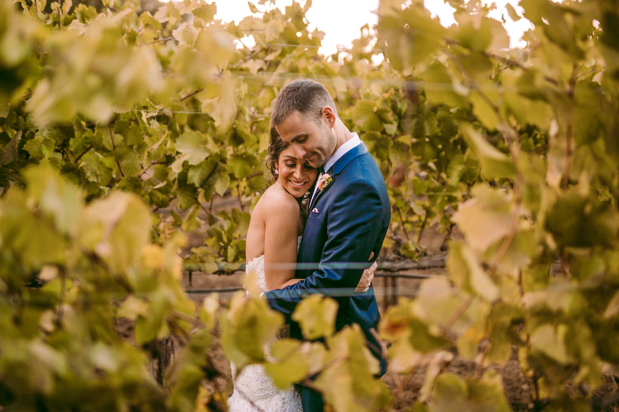 san diego wedding   photographer | bride leaning against groom's chest seen through plantation   row