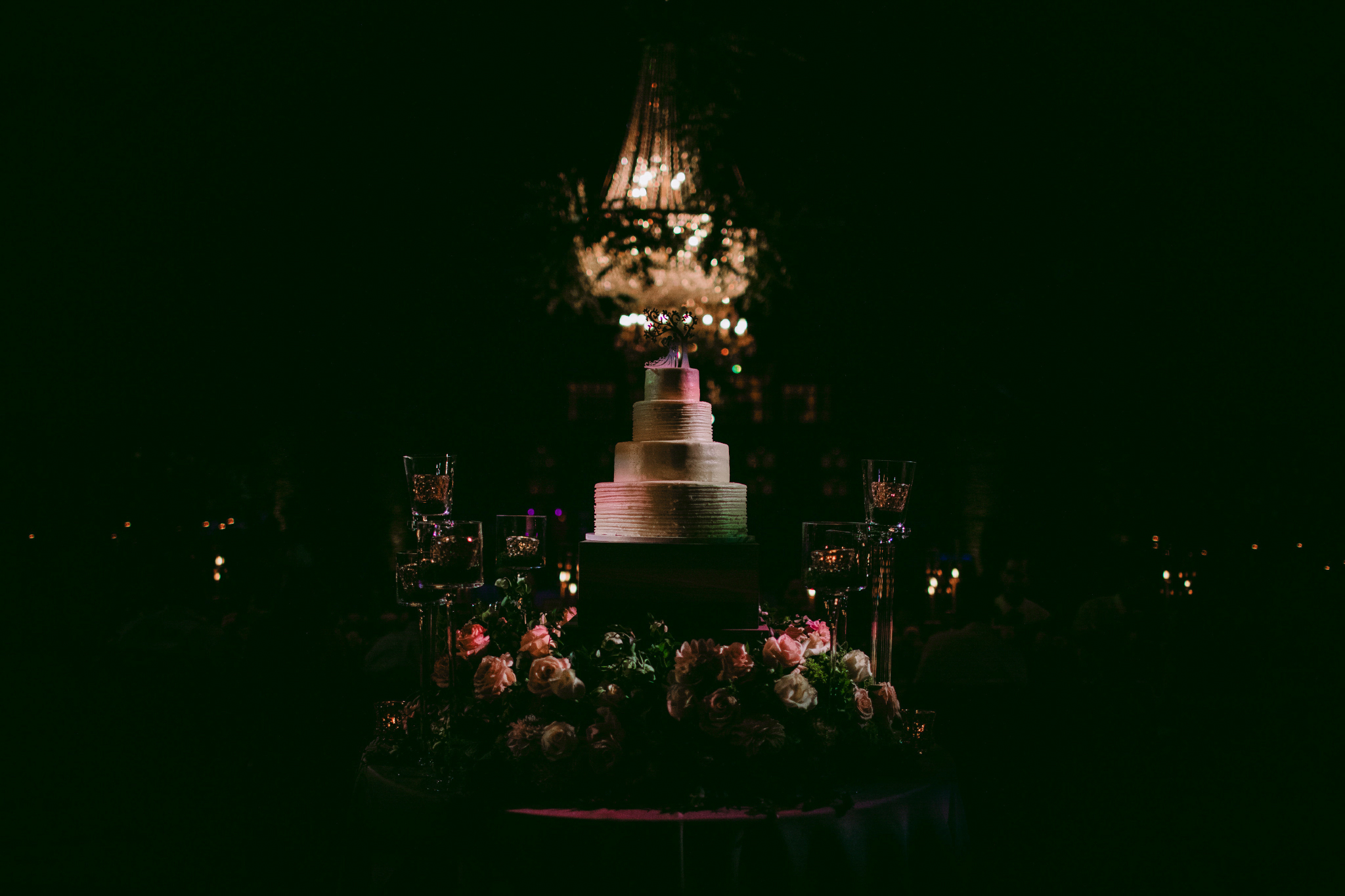 san diego wedding   photographer | low light picture of wedding cake with chandelier in   background