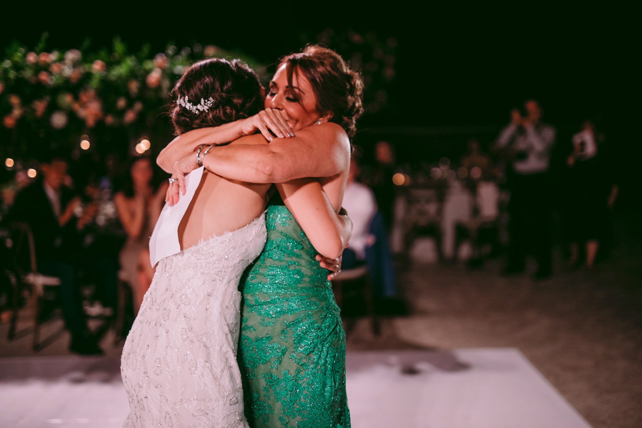san diego wedding   photographer | woman in green dress hugs bride whil holding piece of paper   behind bride