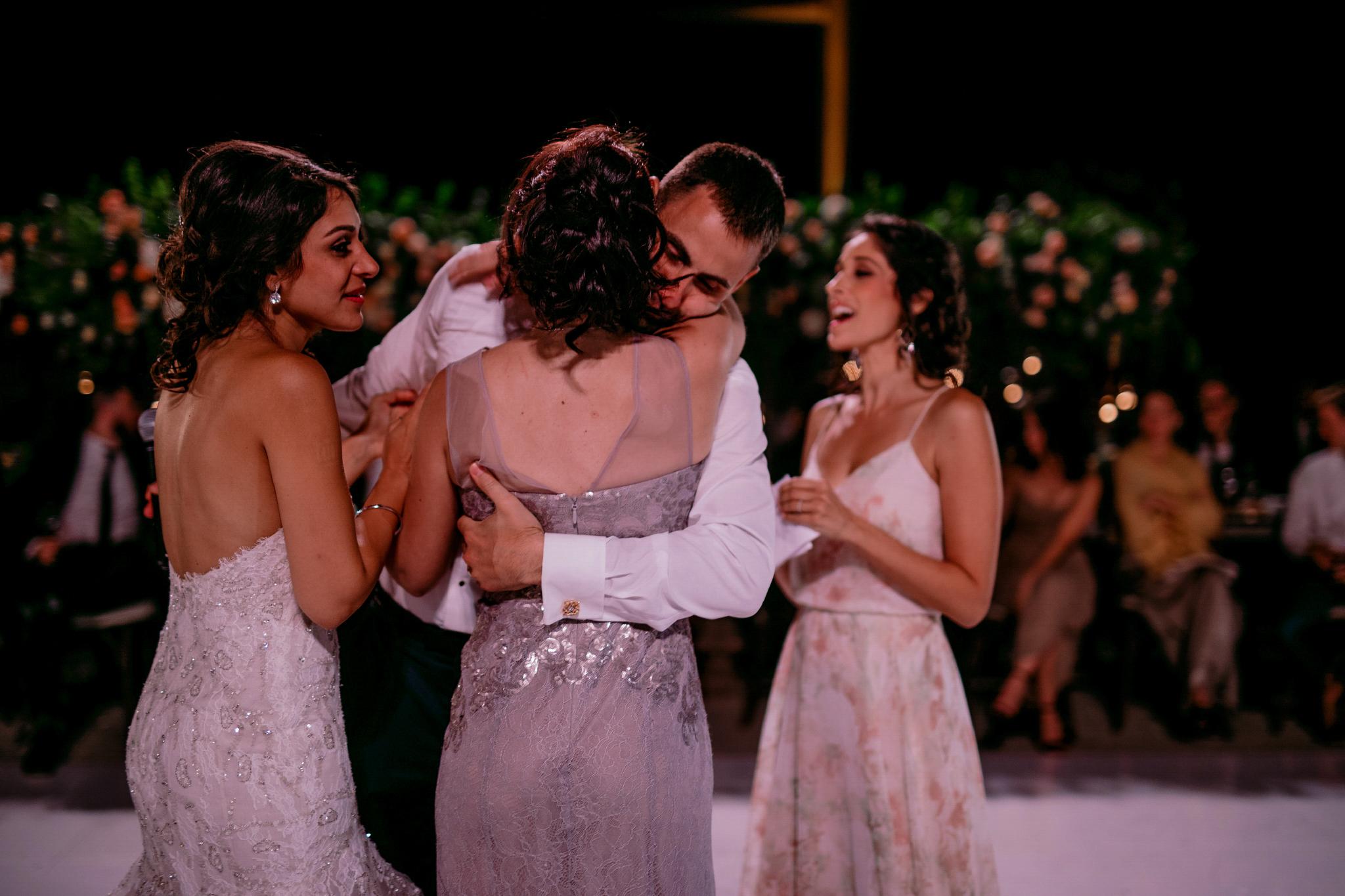 san diego wedding   photographer | groom hugs woman in grey dress while bride looks on