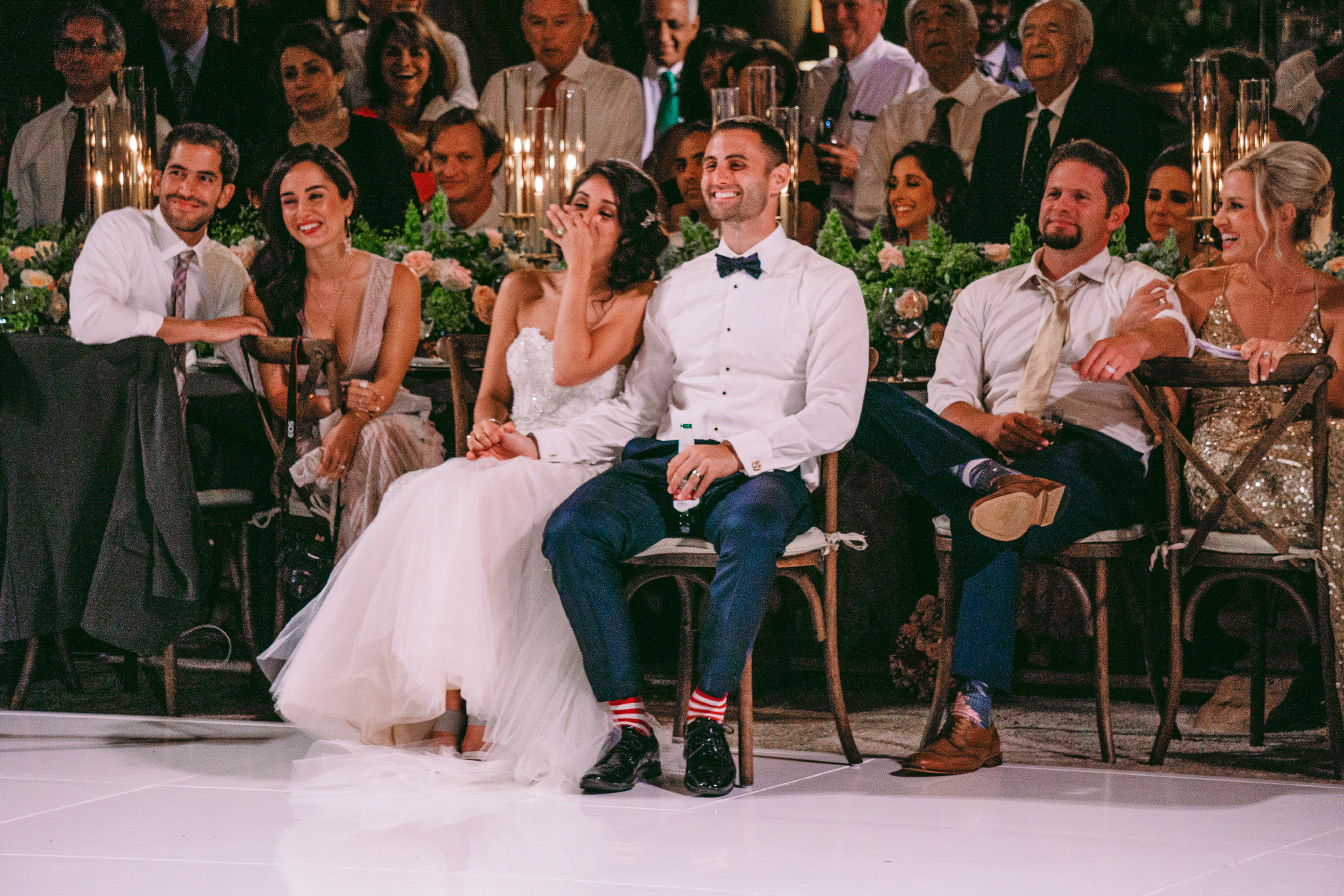 san diego wedding   photographer | married couple casually seated together while laughing with   crowd behind them