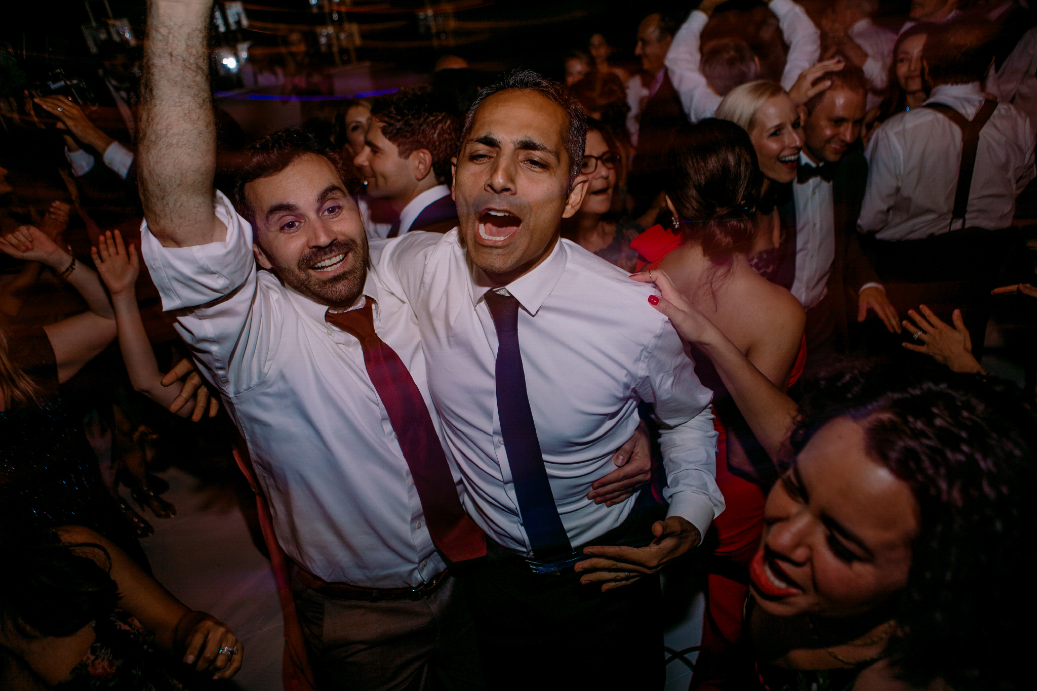 san diego wedding   photographer | 2 men in white shirts and different colored ties dancing   together in the middle of the dance floor