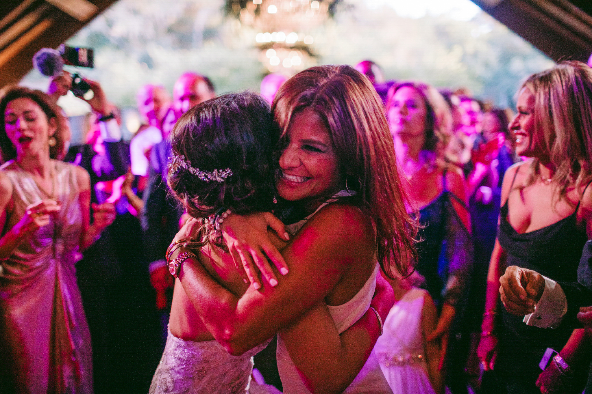 san diego wedding   photographer | man in white dress hugging bride with crowd of people behind   them illuminated with neon pink light