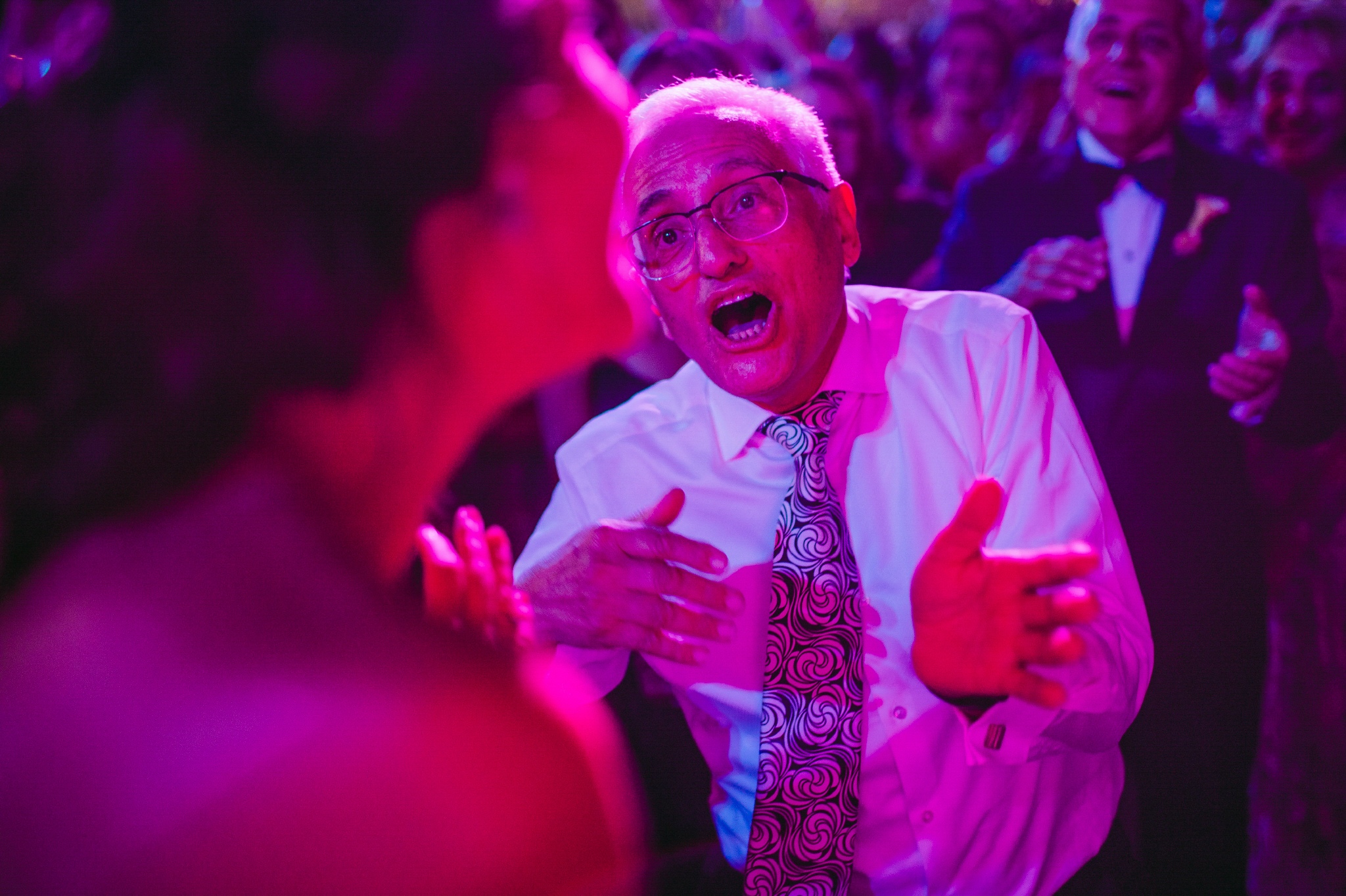 san diego wedding   photographer | old man in white shirt wearing black and white tie dancing in   the middle of a crowd