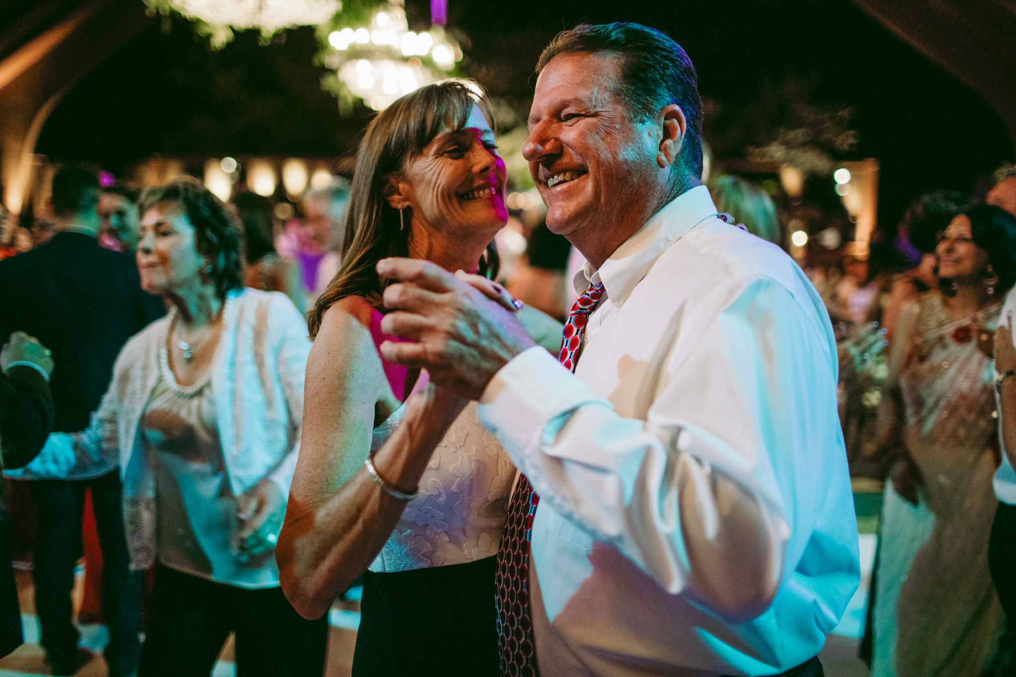 san diego wedding   photographer | old couple wearing white while dancing with crowd in   background