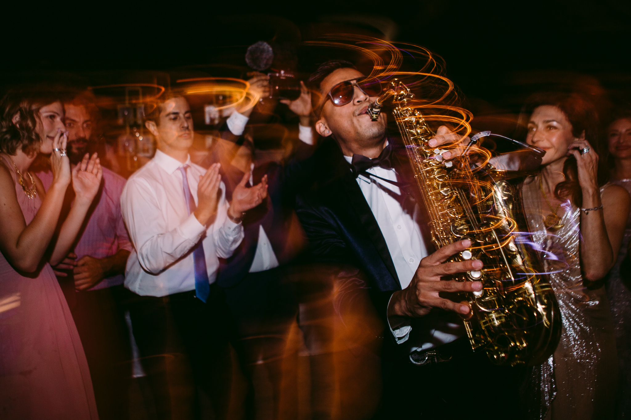 san diego wedding   photographer | long exposure shot of man with saxophone playing in the middle   of a crowd