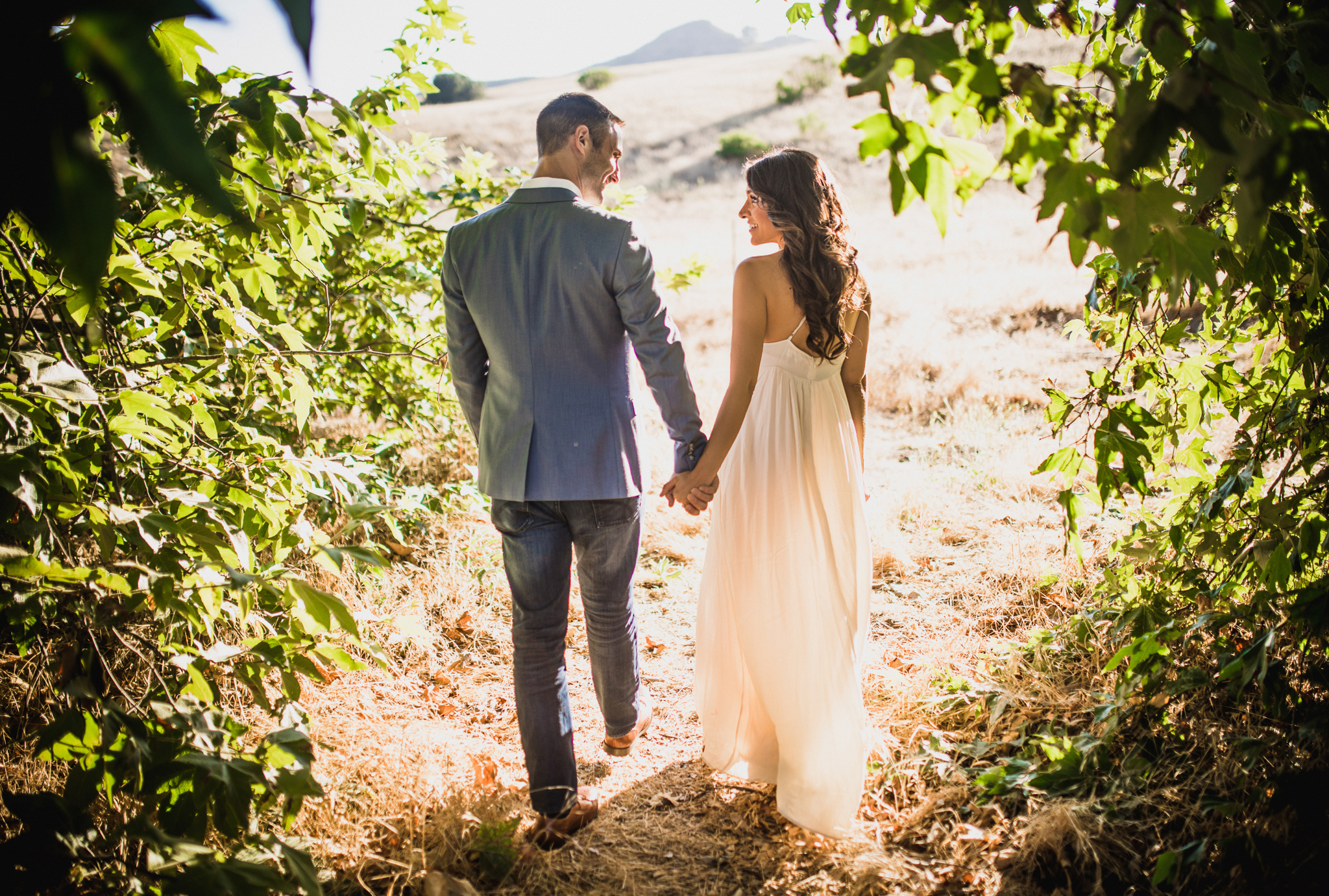 san diego wedding   photographer | couple holding hands looking at each other walking away from   camera