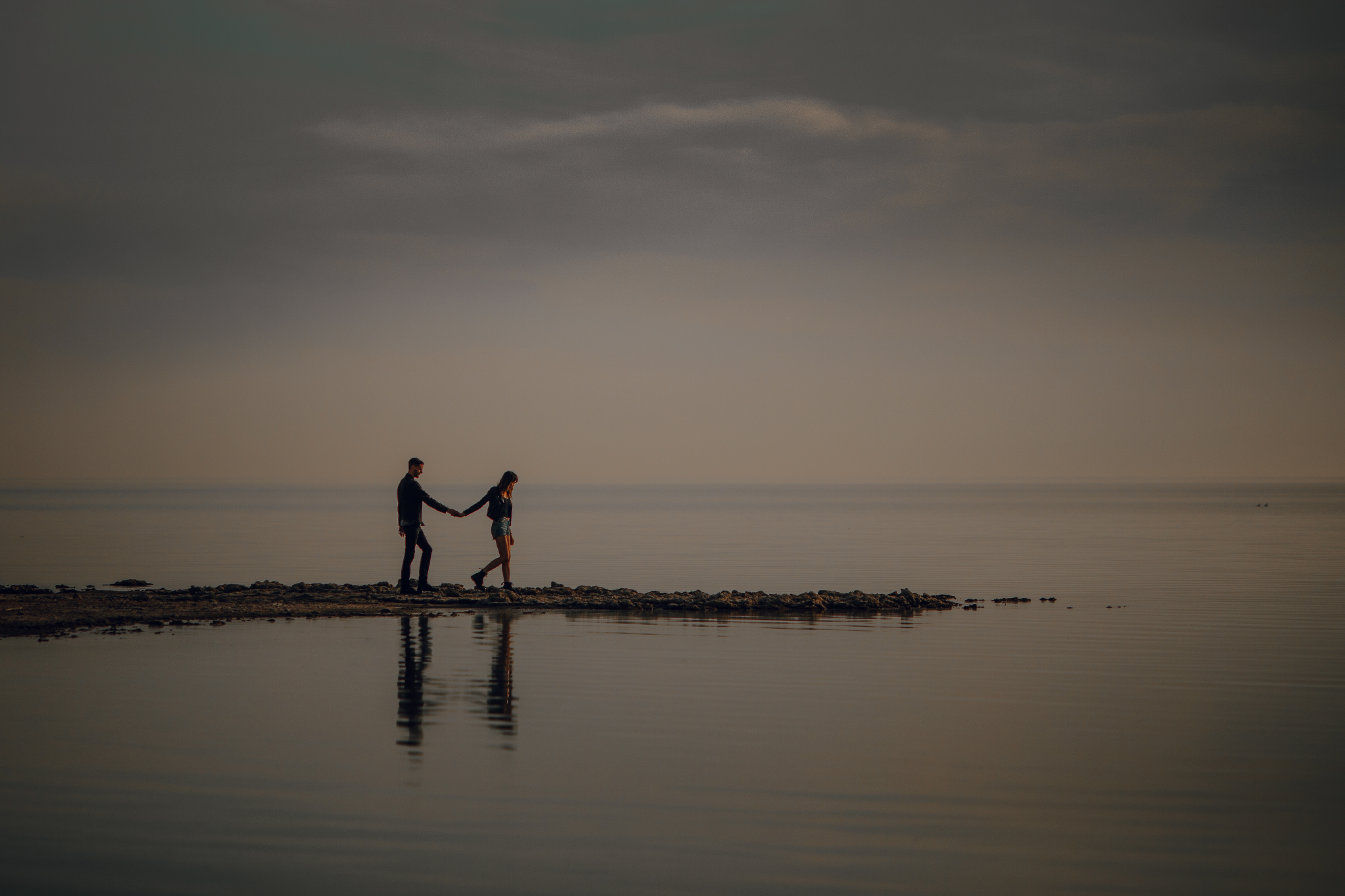 san diego wedding   photographer | woman leading man's way by holding his hand on lake