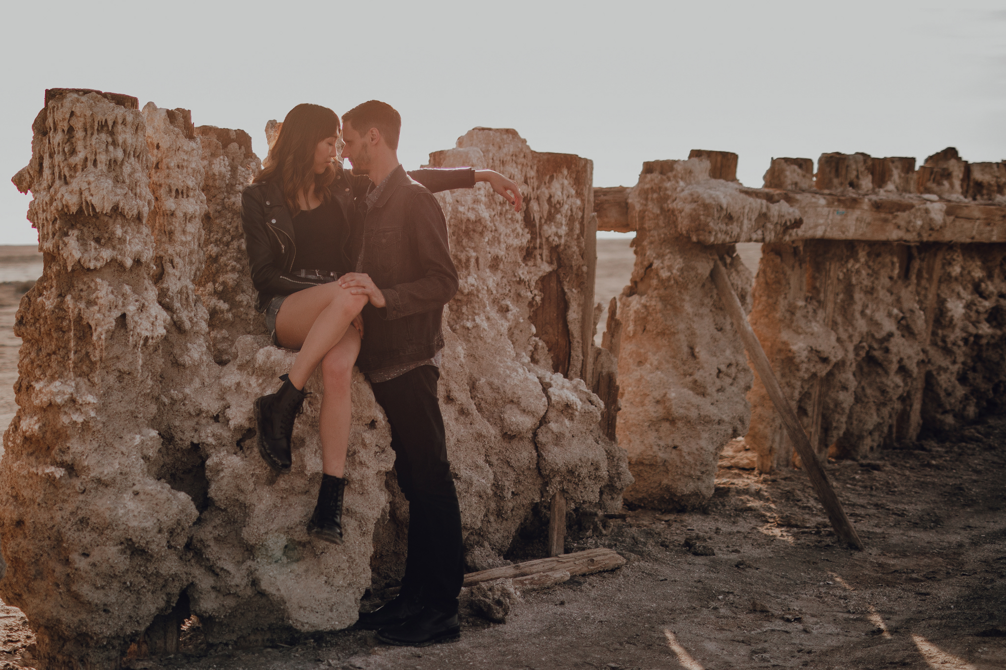 san diego wedding   photographer | woman sitting on sand formation stuck on wooden fence with her   hand on man's shoulder