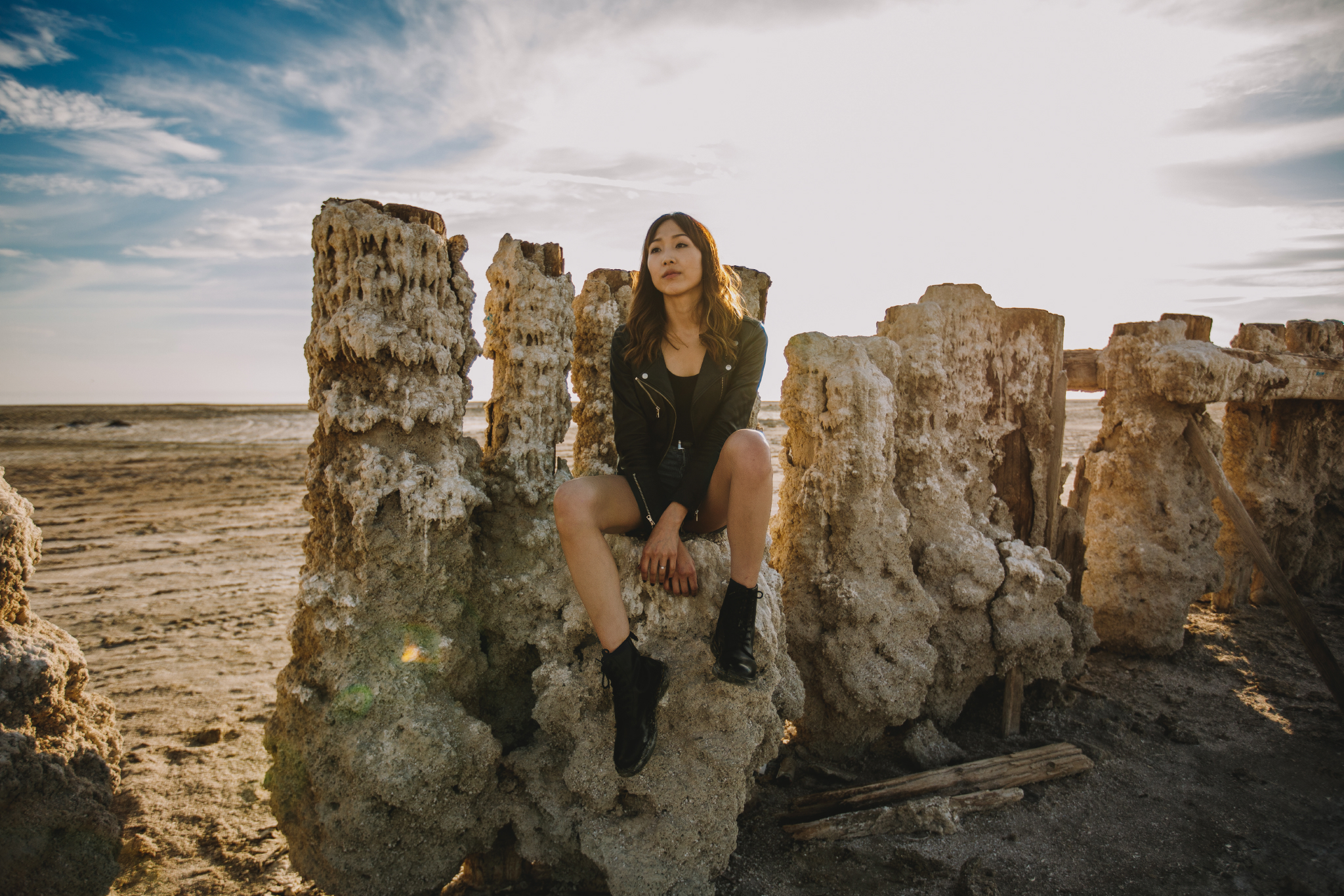 san diego wedding   photographer | woman sitting on sand formation on wooden fence