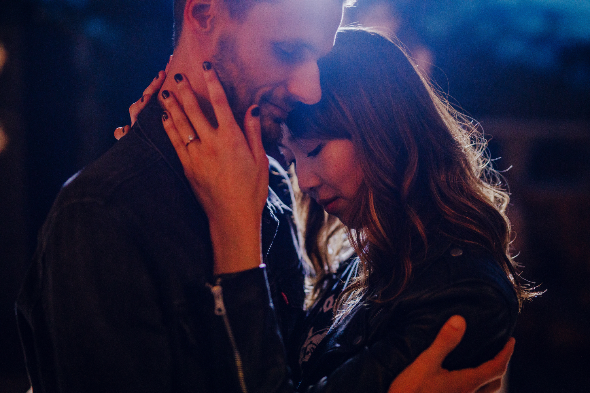 san diego wedding   photographer | couple holding each other while woman hold man's face   illuminated by light behind them