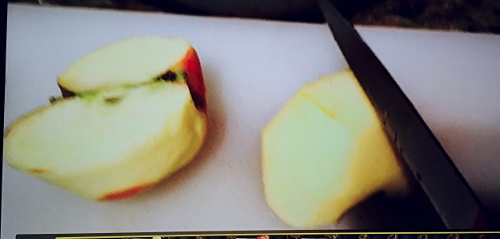 First we cut the apples in half. Then we cut each half in half again.