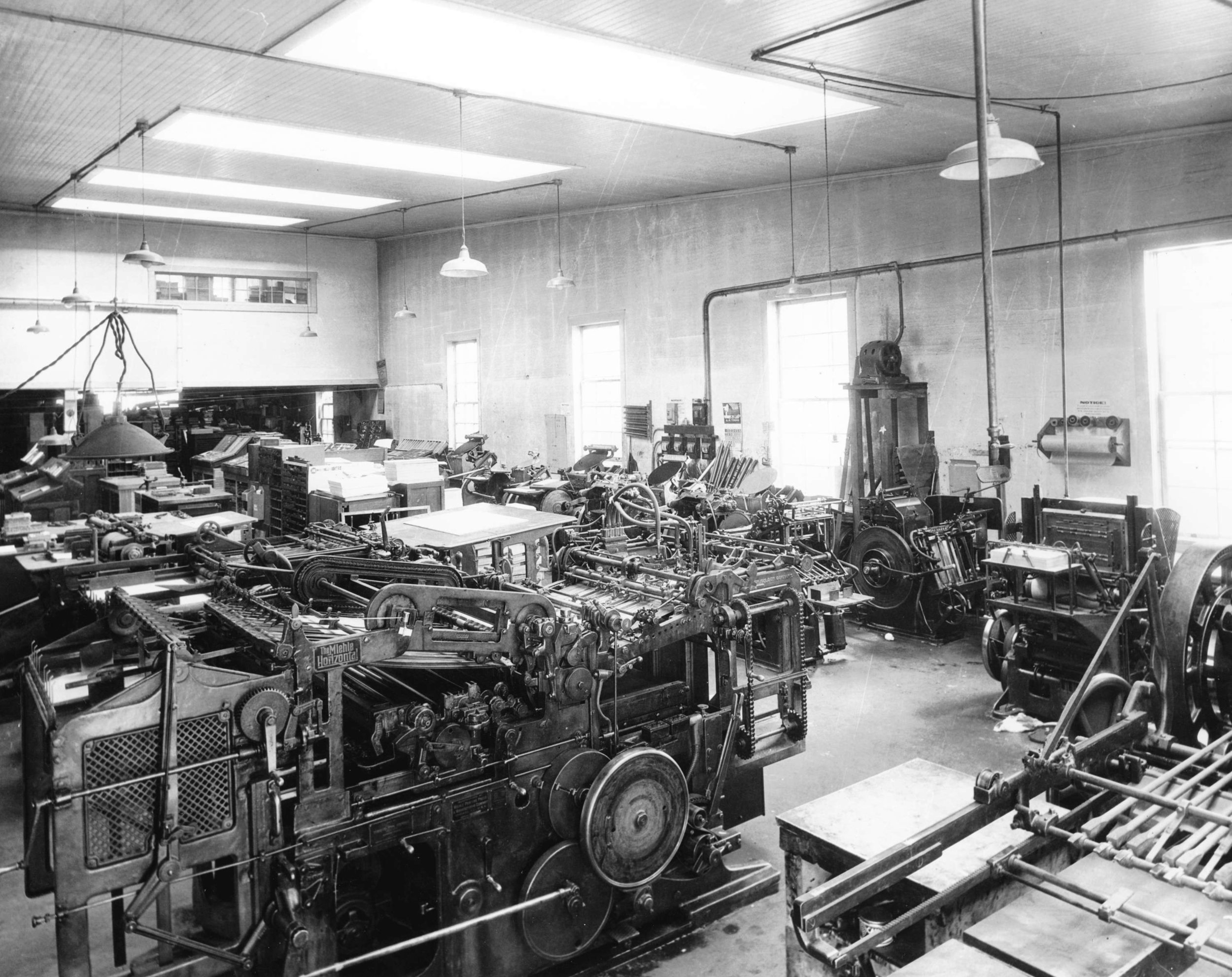 Photo from inside the shop showing the machinery of printing. By Philip T. Timms, courtesy City of Vancouver Archives