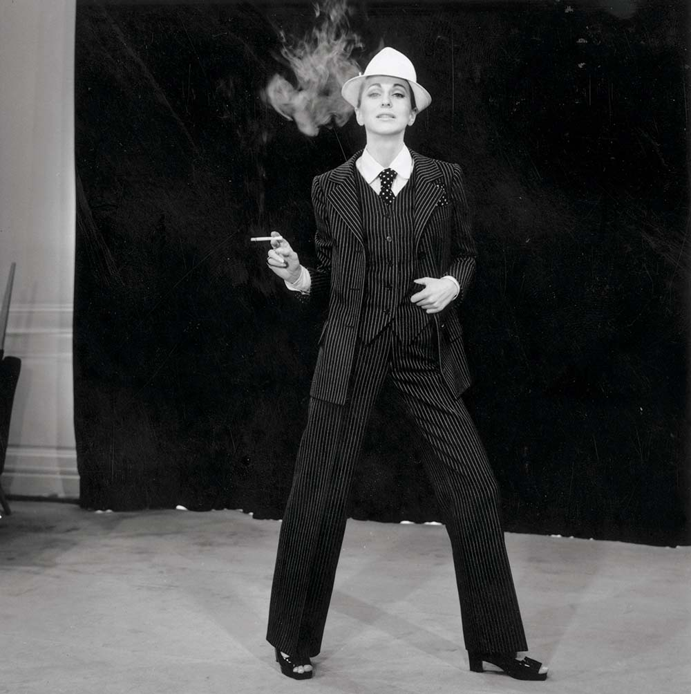 A model showcases a masculine look in a pinstripe trouser suit by Yves Saint Laurent. His Le Smoking suit became a signature piece for the designer