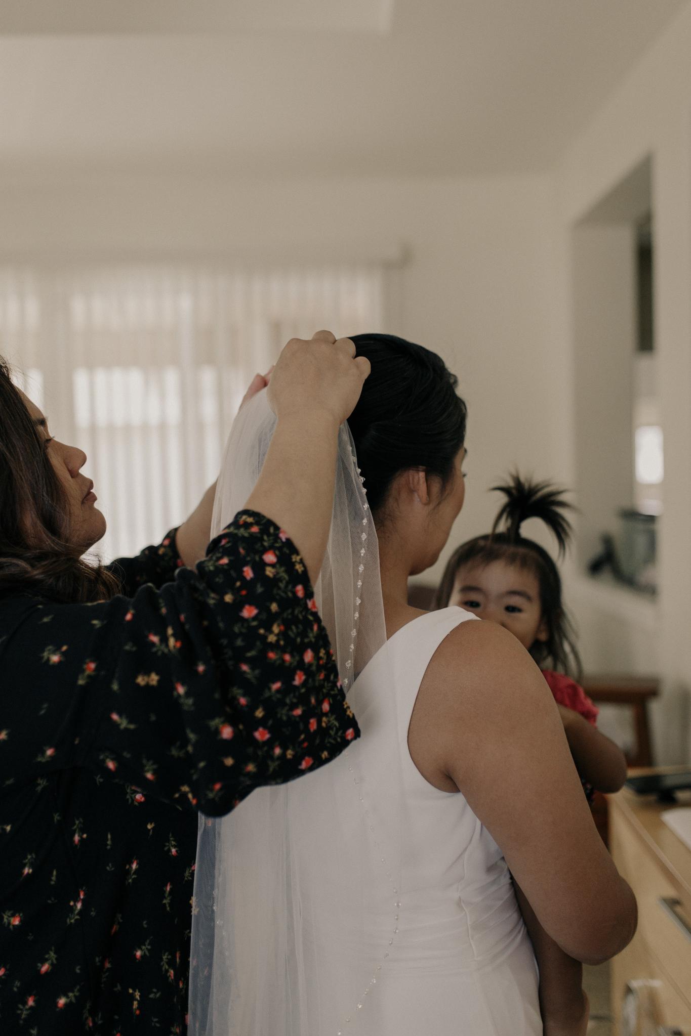 putting on wedding veil photo