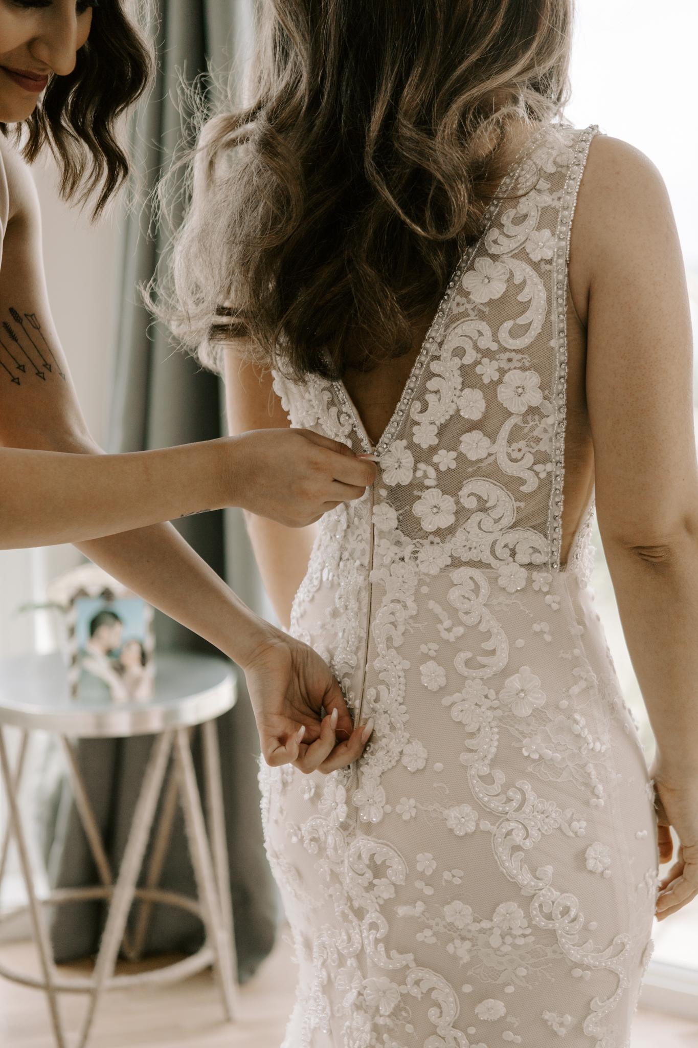 Zipping up bride's dress
