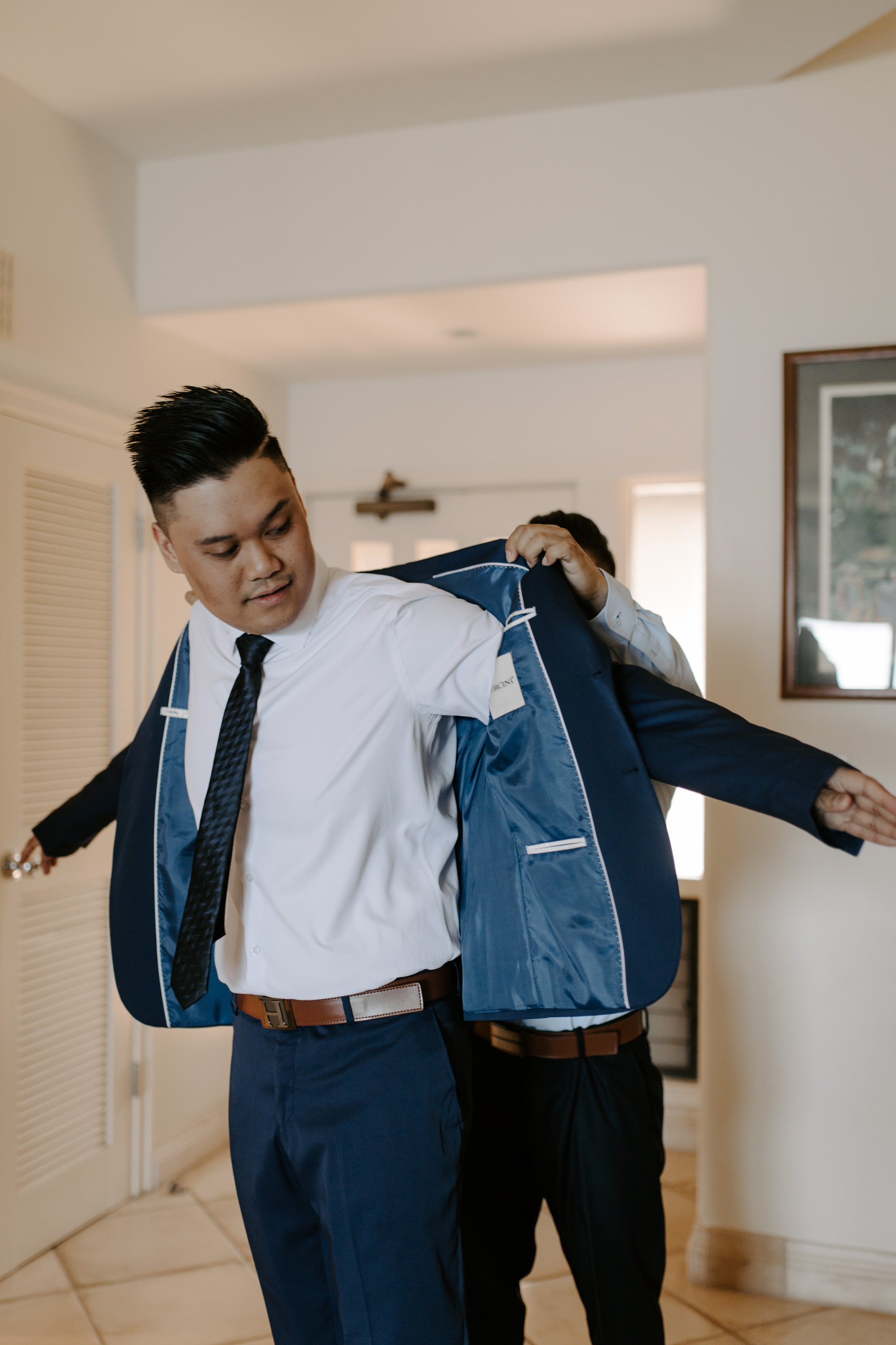 Best man helping groom put on his jacket by Maui Wedding Photographer Desiree Leilani