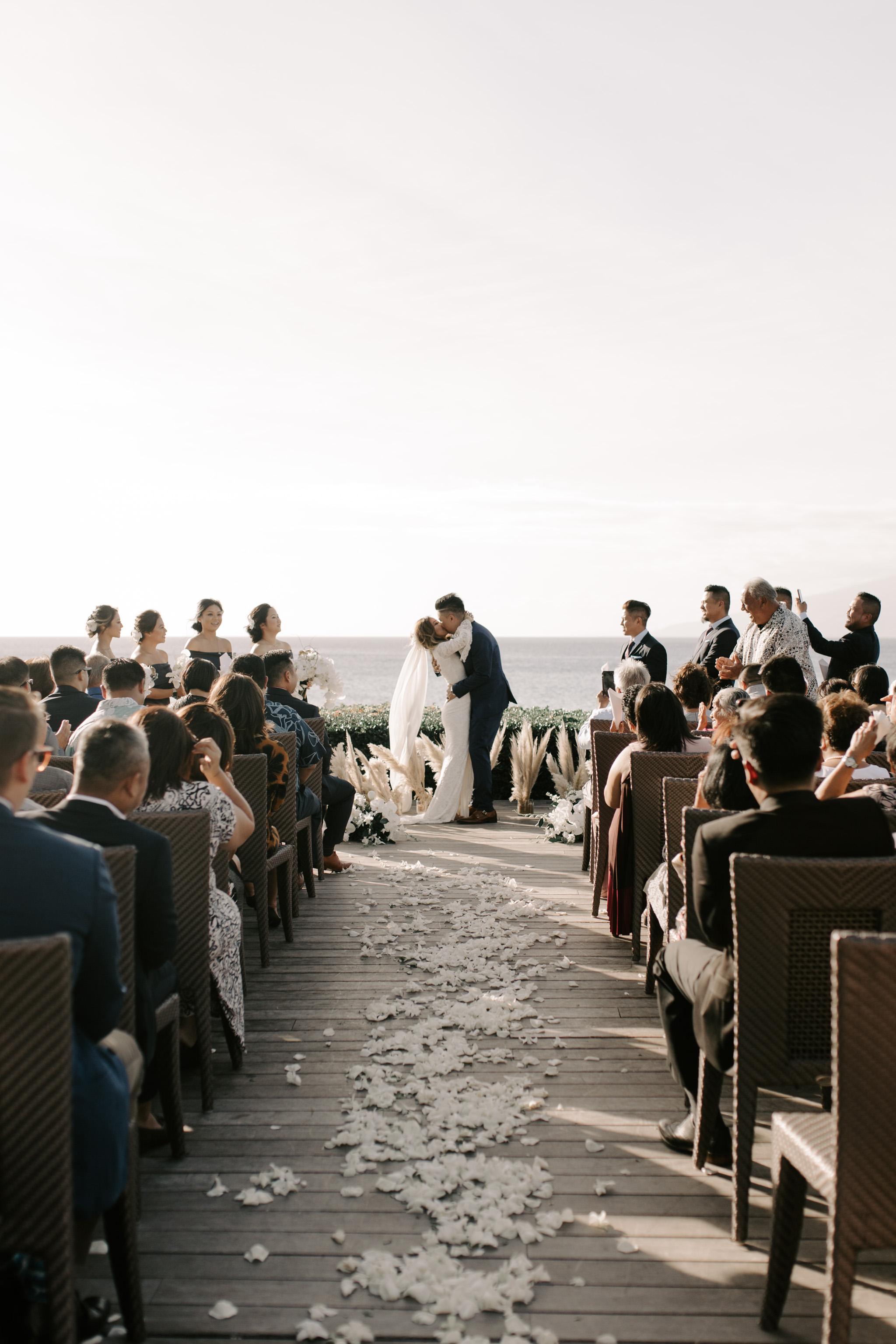 First kiss as husband and wife   Merriman's Kapalua Maui wedding by Hawaii wedding photographer Desiree Leilani