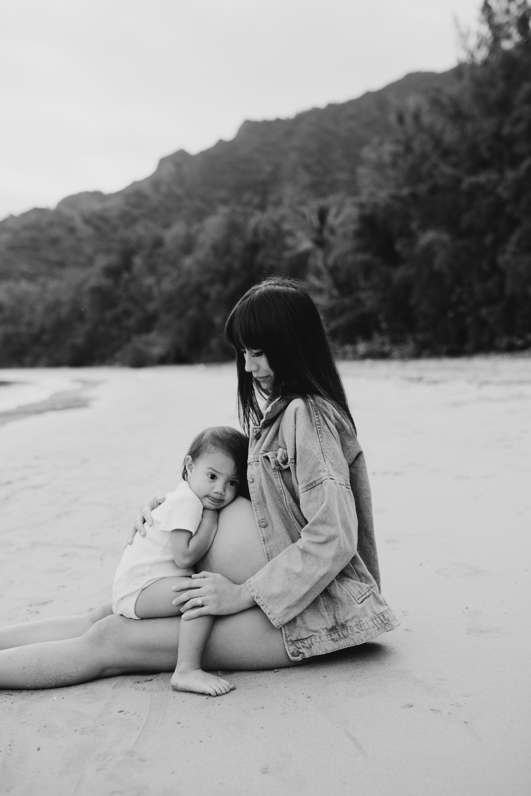Cute maternity photos in a bikini and jean jacket at Kahana Bay by Oahu family photographer Desiree Leilani