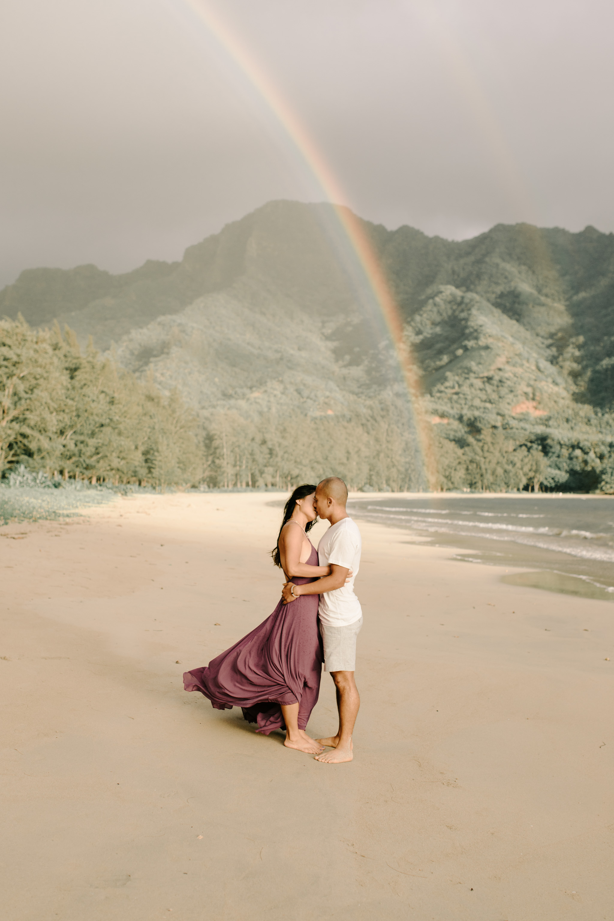 Beautiful Hawaii beach couple photos with a gorgeous rainbow in the background by Oahu couple photographer Desiree Leilani