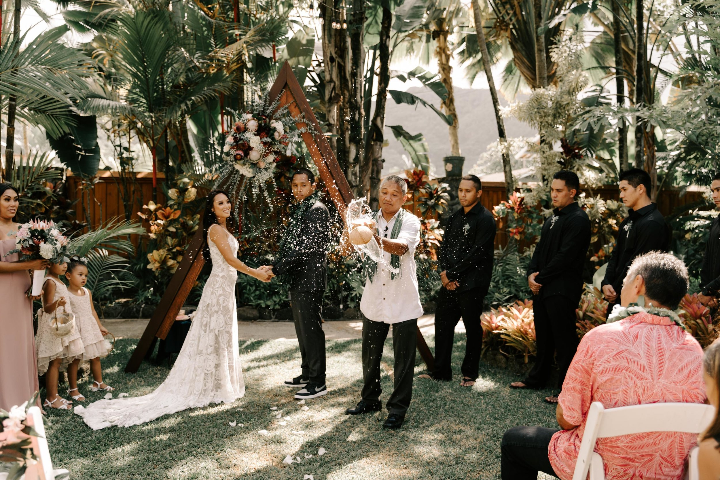 Cracking open a coconut during the wedding ceremony - Hale Koa Phineas Estate Wedding By Hawaii Wedding Photographer Desiree Leilani
