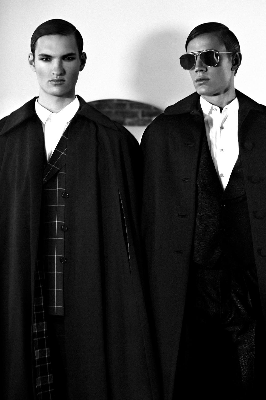 Tom: Suit  New & Lingwood , Shoes  Giuseppe Zanotti , Shirt  Topman . Patrick: Suit  Joshua Kane , Shirt  Topman , Cape  Vintage Nina Ricci , Sunglasses  Thom Browne .