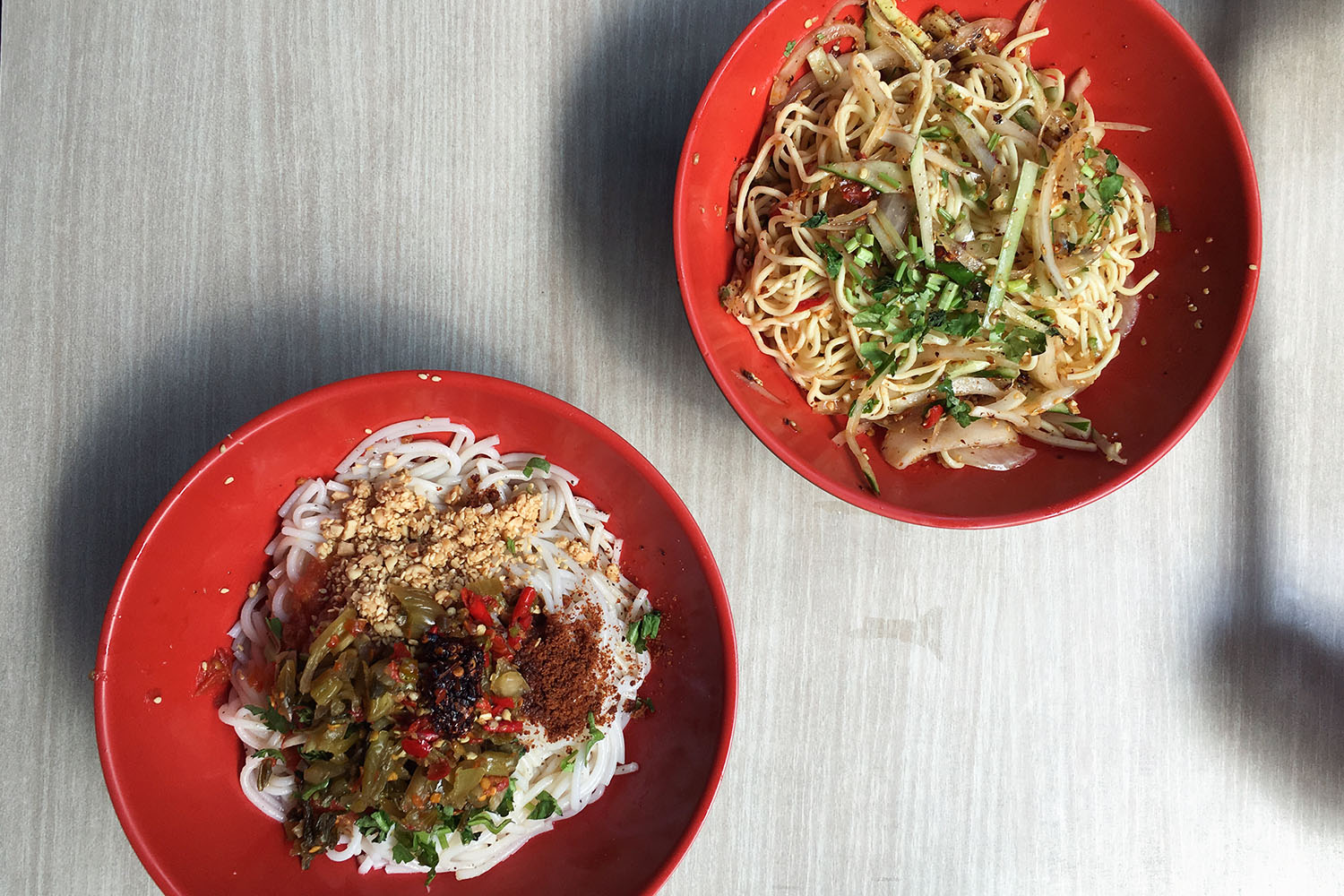 The best meal I had all summer: On the left, hot rice noodles with toasted chickpea flour, pickled mustard greens, herbs, lots and lots of chili, and a tomato-onion chutney/sauce; on the right, cold snappy egg or alkaline noodles with cucumber, herbs, raw onion, toasted seeds and chili.