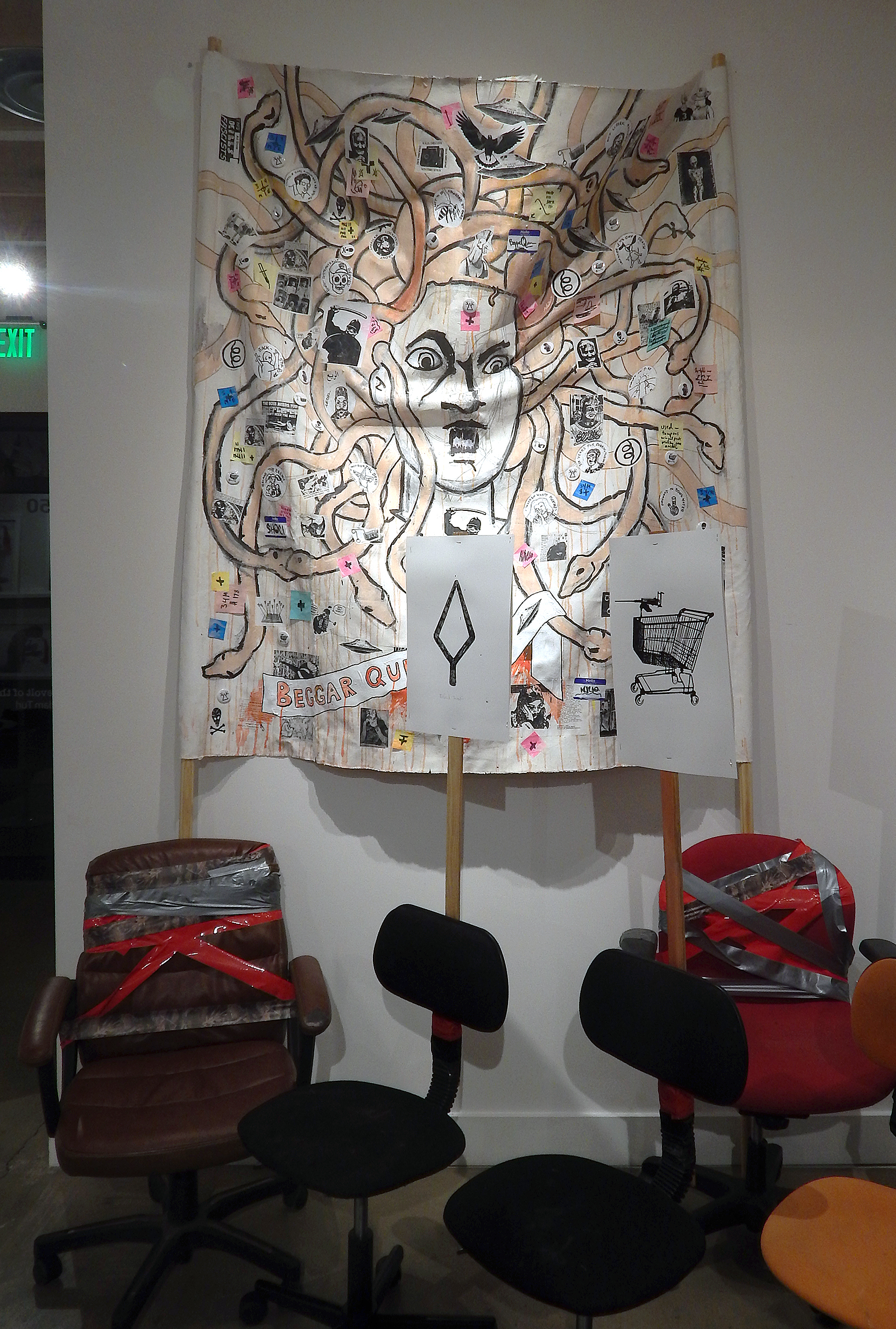 Beggar Queen.  Acrylic, stickers, marker, photocopies, buttons, post-it notes, coffee and mixed media on canvas banner with poles (installation view). (2017-2018) (Adam Turl)