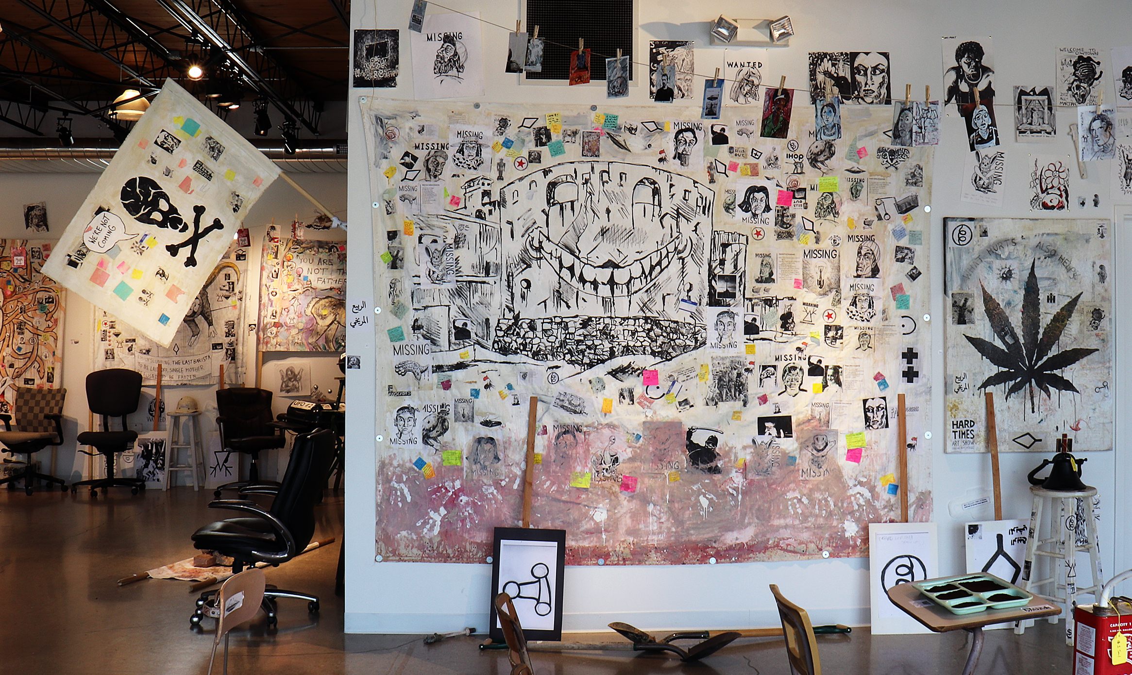 Ohio Erasure Castle (The Barista Who Disappeared)  by Adam Turl. Acrylic, marker, Sharpie, clay slip, photocopies, stickers, post-it notes, coffee and mixed media on canvas tarp.Also in foreground,  What Hurts Also Helps  (left) and  Alien Space Pirates Flag  (right).