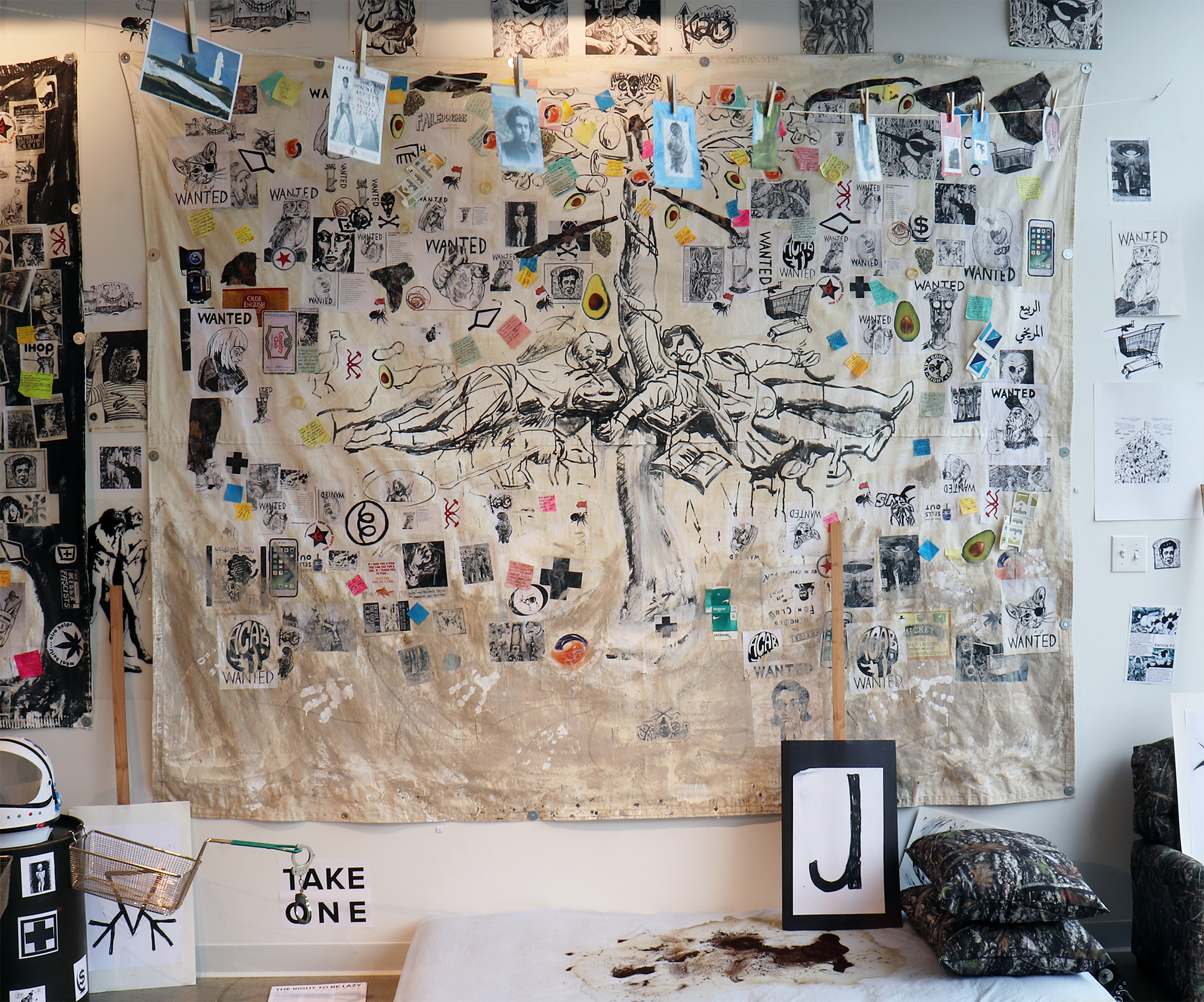 New Lubberland (The Barista Who Disappeared),  by Adam Turl .  Acrylic, marker, Sharpie, clay slip, condoms, photocopies, stickers, coffee, post-it notes, camo and mixed media on canvas tarp (2018).