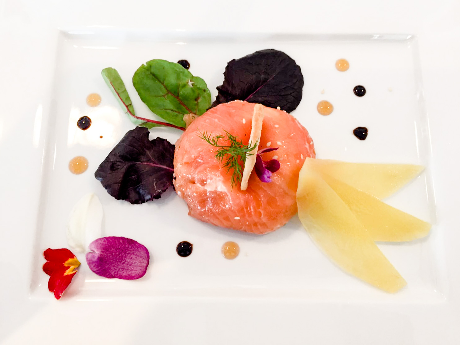 Entrée de printemps: dôme de saumon frais accompagné de céleri, mangue et fleurs de saison