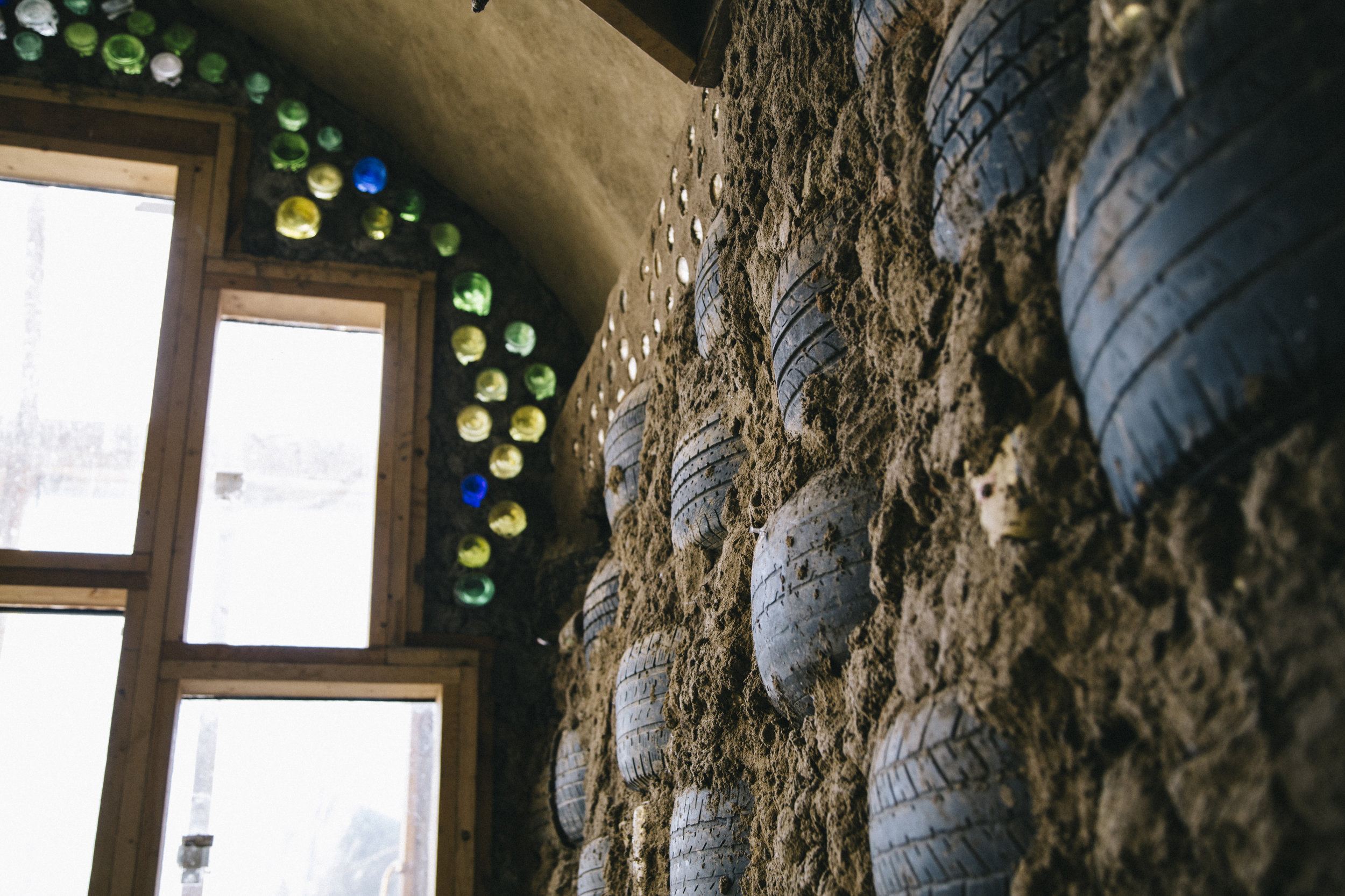 A wall made up of rammed-earth tires, and the colored jewels of light passing through bottle bricks.