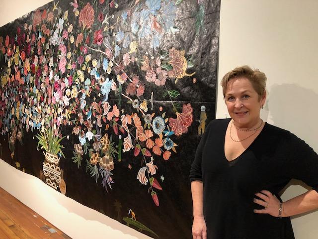 Gallery owner, Kim Weinberger, with Cornucopia #3 by Nancy Friedemann-Sánchez